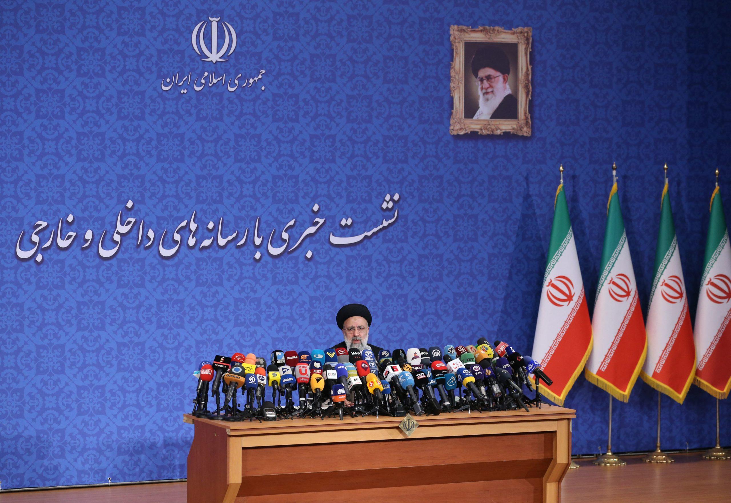 Iranian President-elect Ebrahim Raisi sits under a portrait of the Islamic republic's supreme leader Ayatollah Ali Khamenei on June 21. (Atta Kenare/AFP via Getty Images)