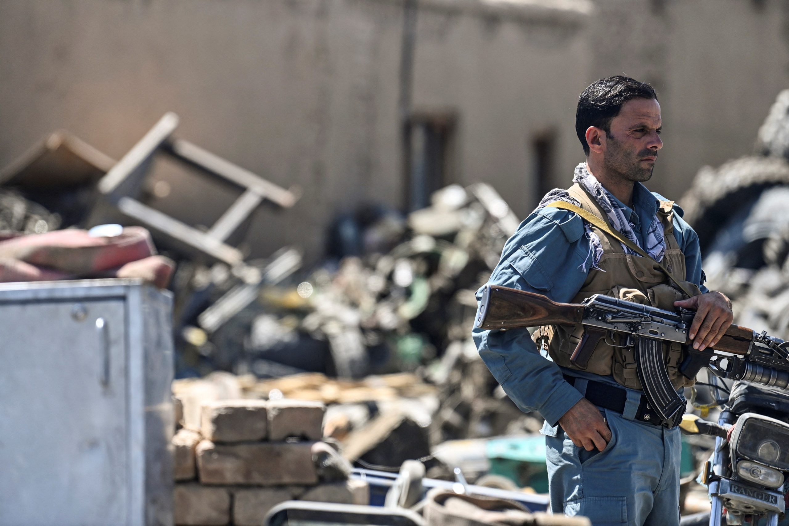 In this picture taken on June 17, 2021, a policeman stands guard at a junkyard near the Bagram Air Base in Bagram. (ADEK BERRY/AFP via Getty Images)