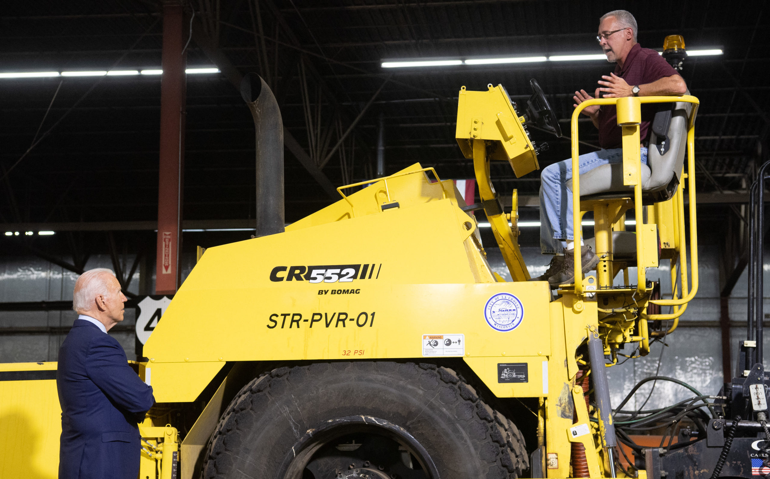 President Joe Biden speaks with a worker who sits on top of a road repair machine during a tour of the La Crosse Municipal Transit Utility in La Crosse, Wisconsin, on Tuesday. (Saul Loeb/AFP via Getty Images)
