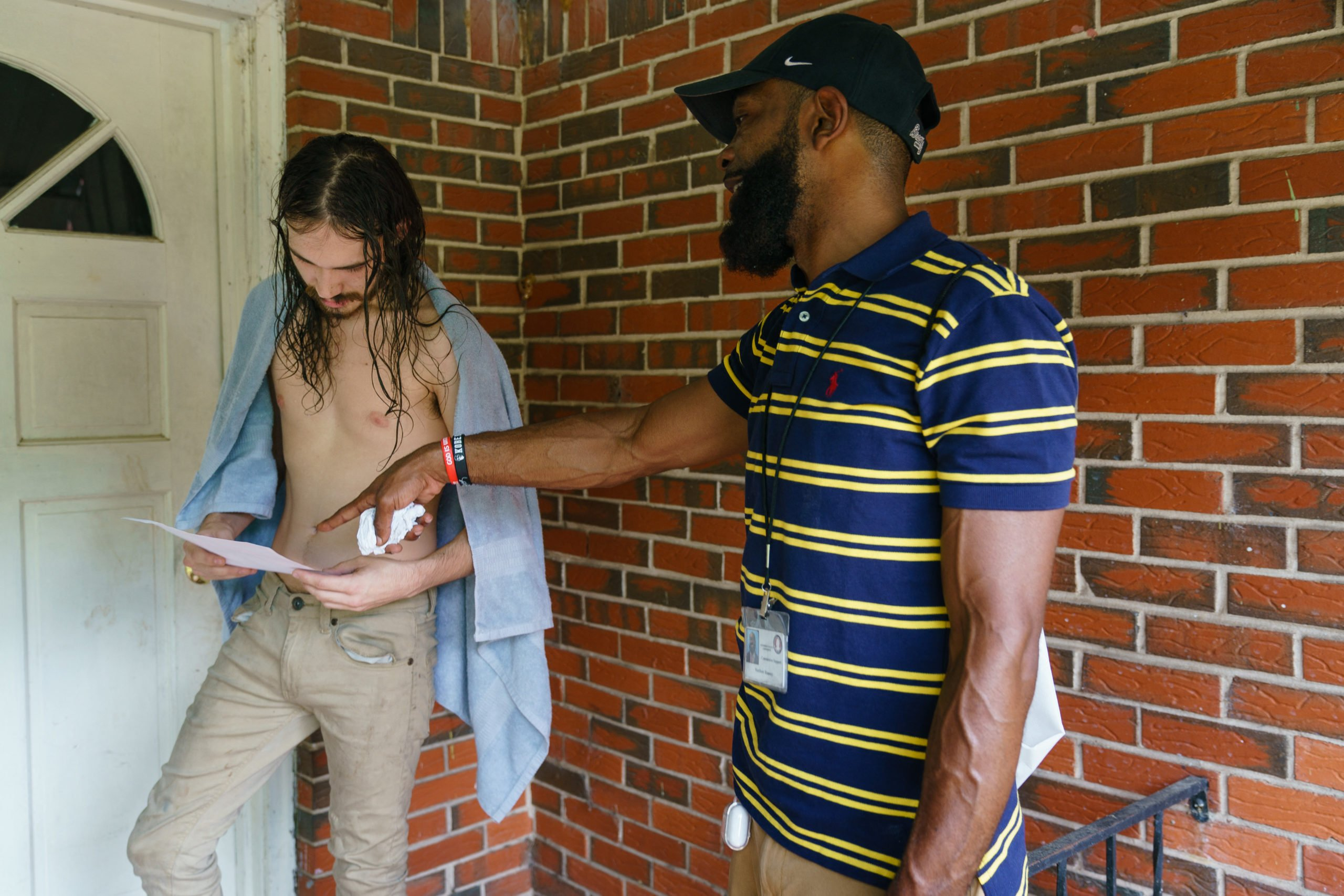 A staff member of City Councilwoman Sheila Tyson speaks to a resident during a door-knocking outreach effort to inform people about an upcoming COVID-19 vaccination event, on Wednesday, June 30, 2021, in Birmingham, Alabama. (ELIJAH NOUVELAGE/AFP via Getty Images)