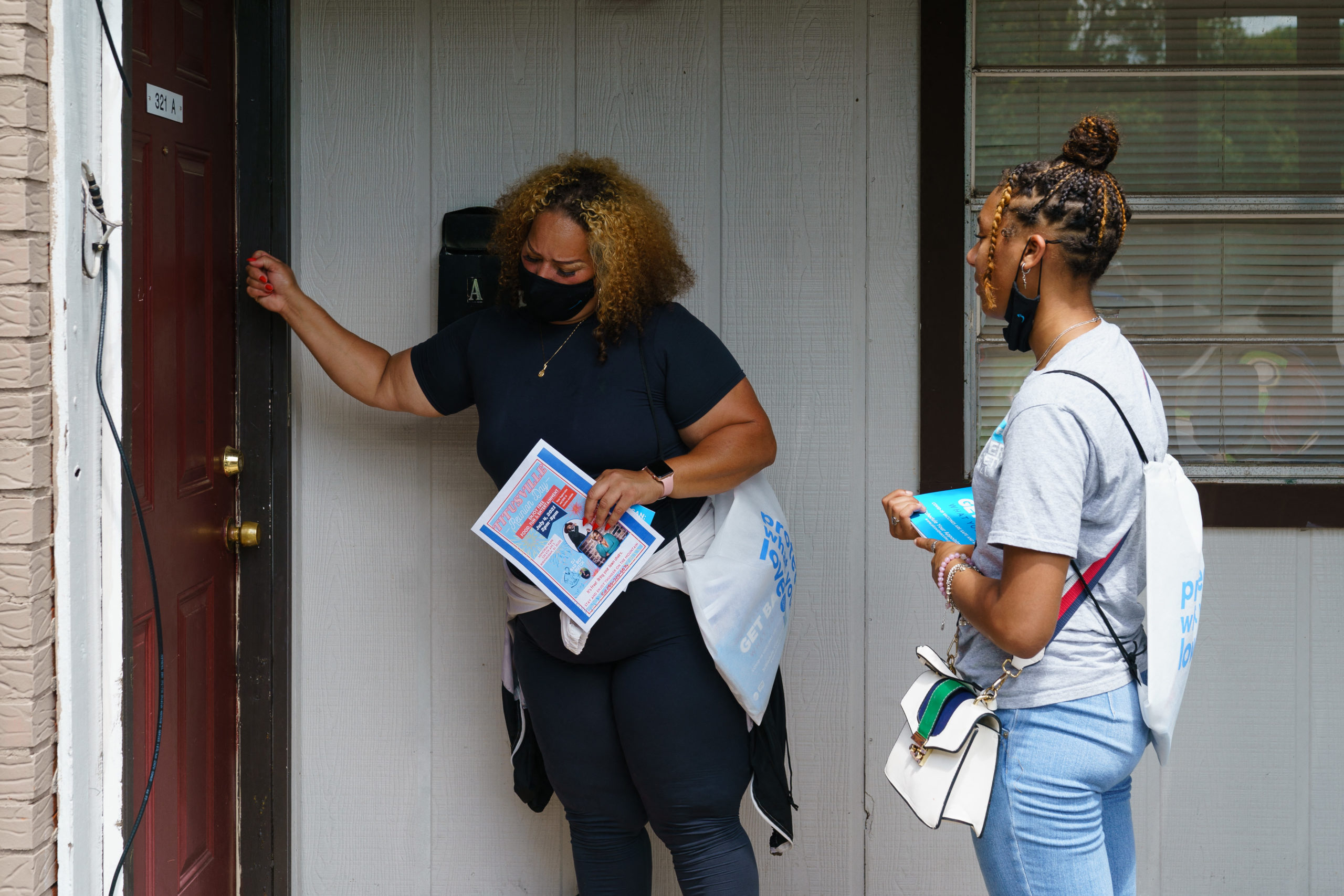 Volunteers and staffers knock on a door during an outreach effort to inform residents about an upcoming COVID-19 vaccination event, on June 30, 2021, in Birmingham, Alabama. (ELIJAH NOUVELAGE/AFP via Getty Images)