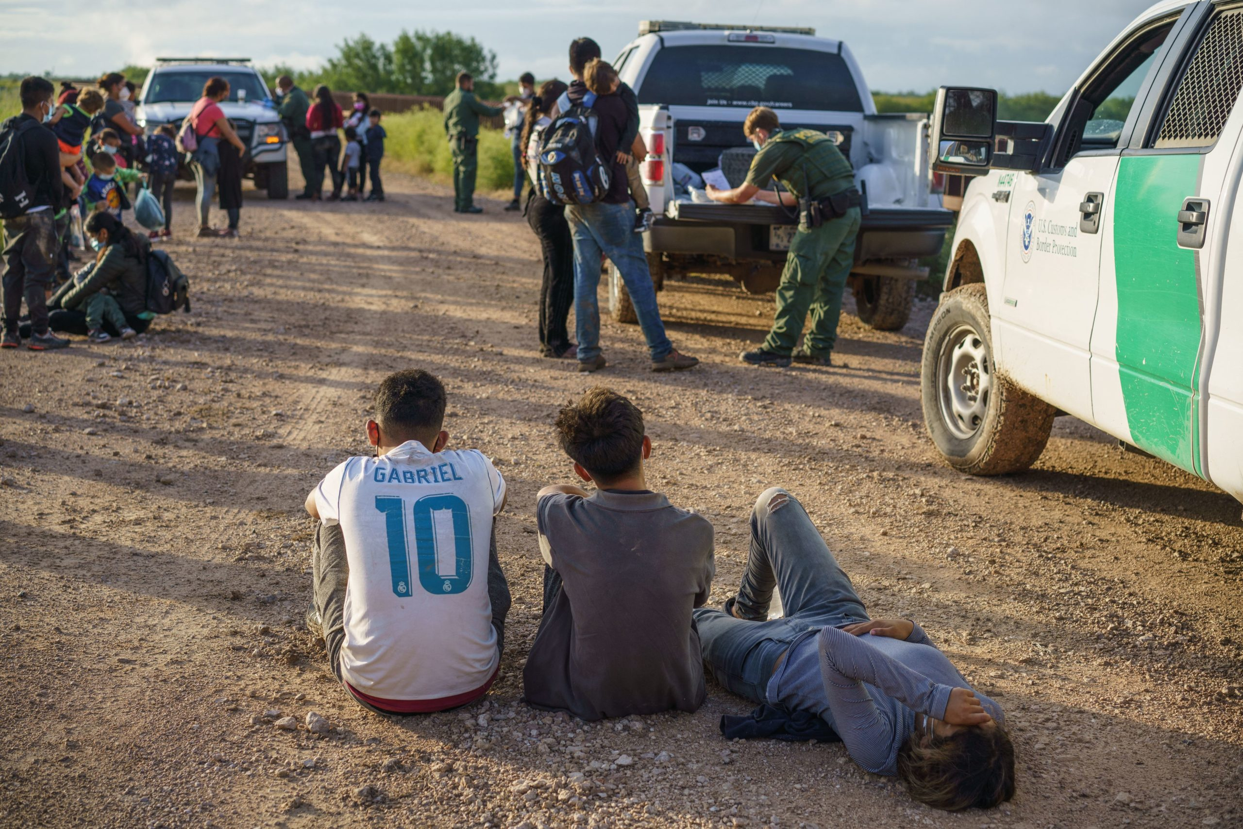Migrants wait to be processed by the United States Border Patrol after crossing the US-Mexico border into the United States in Penitas, Texas on July 8, 2021. (Photo by PAUL RATJE/AFP via Getty Images)