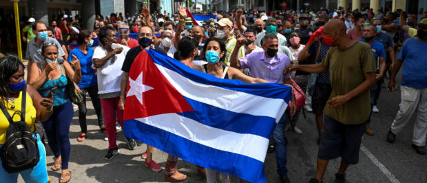 """TOPSHOT - People take part in a demonstration to support the government of the Cuban President Miguel Diaz-Canel in Havana, on July 11, 2021. - Thousands of Cubans took part in rare protests Sunday against the communist government, marching through a town chanting """"Down with the dictatorship"""" and """"We want liberty."""" (Photo by YAMIL LAGE / AFP) (Photo by YAMIL LAGE/AFP via Getty Images)"""