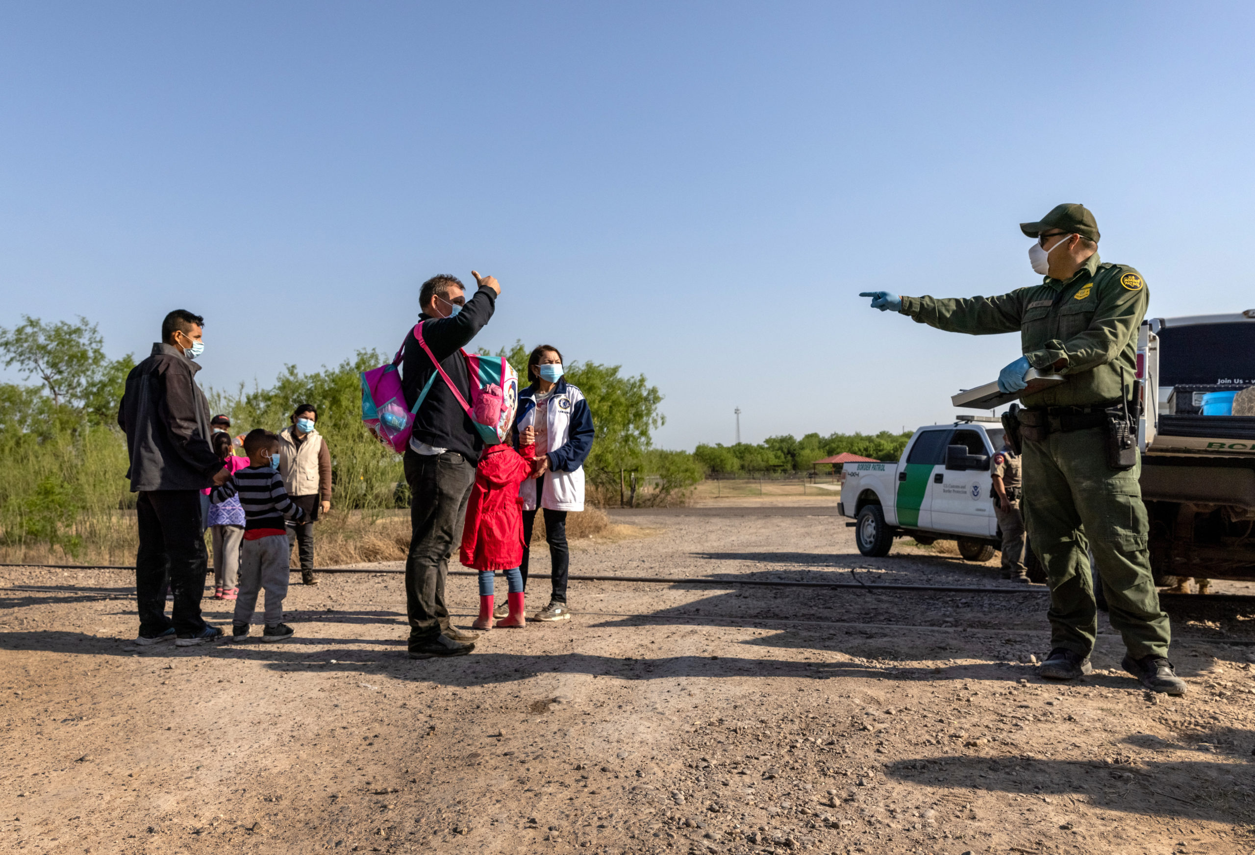 A U.S. Border Patrol agent speaks with a Venezuelan family after they crossed the border from Mexico into the United States on March 26, 2021 in Penitas, Texas. (Photo by John Moore/Getty Images)