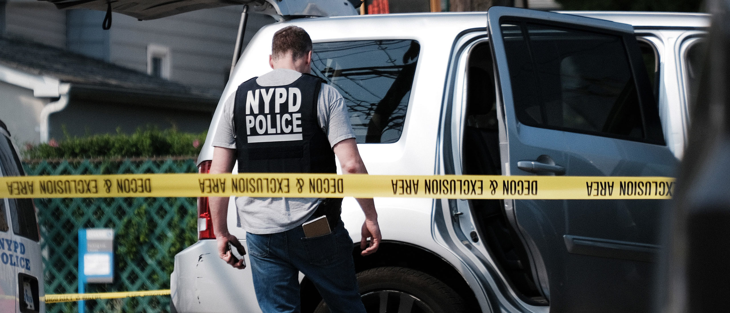 NEW YORK, NEW YORK - JULY 08: Police search a car following a stand-off in front of the 45th Police Precinct in the Bronx on July 08, 2021 in New York City. An armed man in an SUV brandished a gun in front of the precinct with reports of shots fired before he was apprehended. Eric Adams, the democratic winner of the mayoral primary and the likely next mayor of New York City, has promised to step-up searches for illegal guns and to bring back an undercover unit of officers. (Photo by Spencer Platt/Getty Images)