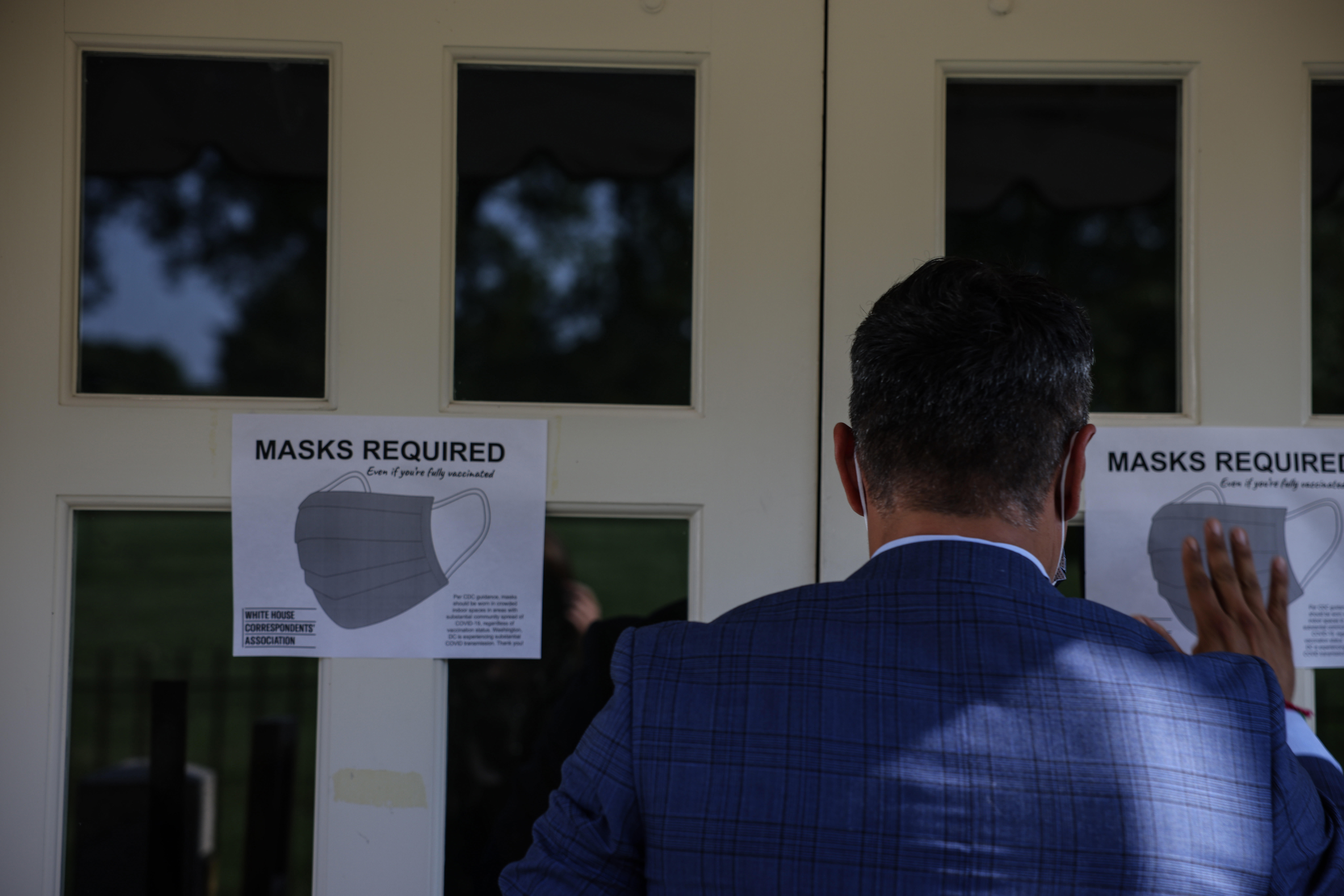 WASHINGTON, DC - JULY 27: Fin Gomez, a journalist with CBS News and White House Correspondents Association (WHCA) board member, replaces signs for mask-wearing guidance around the James Brady Press Briefing Room at the White House on July 27, 2021 in Washington, DC. The White House announced it was reimposing its mask mandate after the CDC advised that fully-vaccinated people should wear masks indoors in areas with possible high spread of COVID-19. (Photo by Anna Moneymaker/Getty Images)