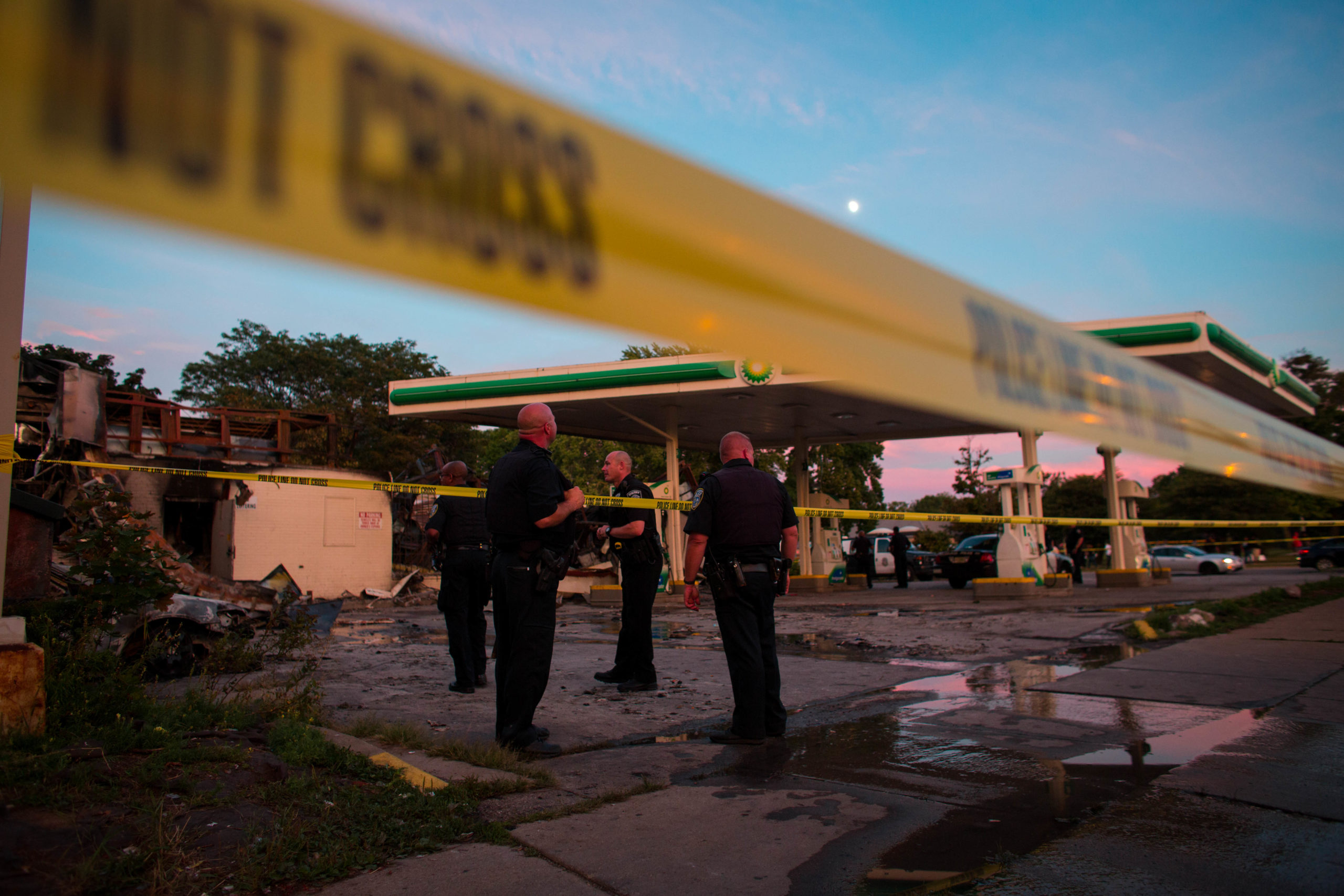 Police officers stand guard as crowds gather for a second night near the BP gas station that was burned after an officer-involved killing August 14, 2016 in Milwaukee, Wisconsina. (Photo by Darren Hauck/Getty Images)
