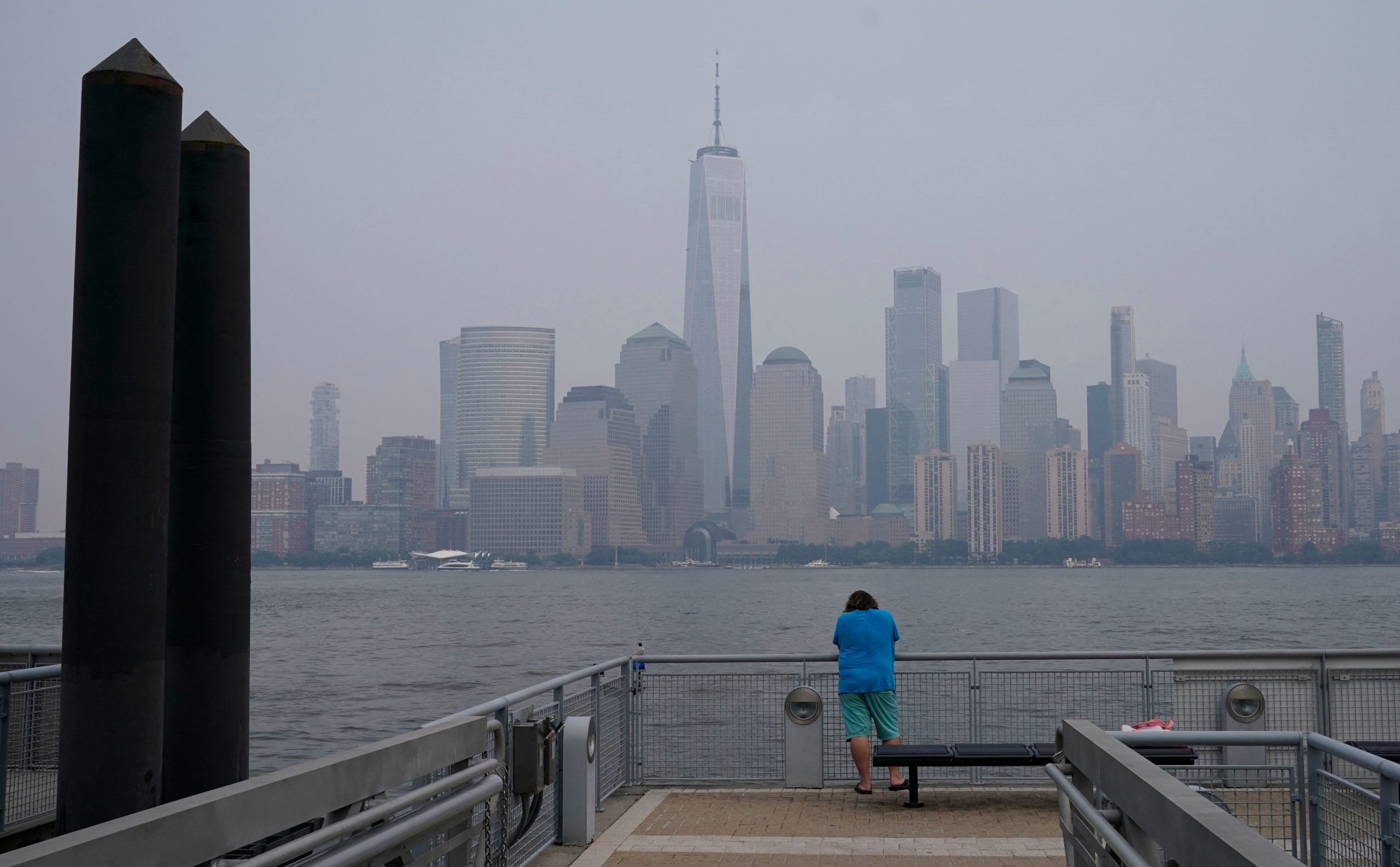 A man waits on the pier in Exchange Place in Jersey City, New Jersey on July 20, 2021 as New York officials issue a air quality health advisory due to the west coast wildfires. (Photo by TIMOTHY A. CLARY/AFP via Getty Images)