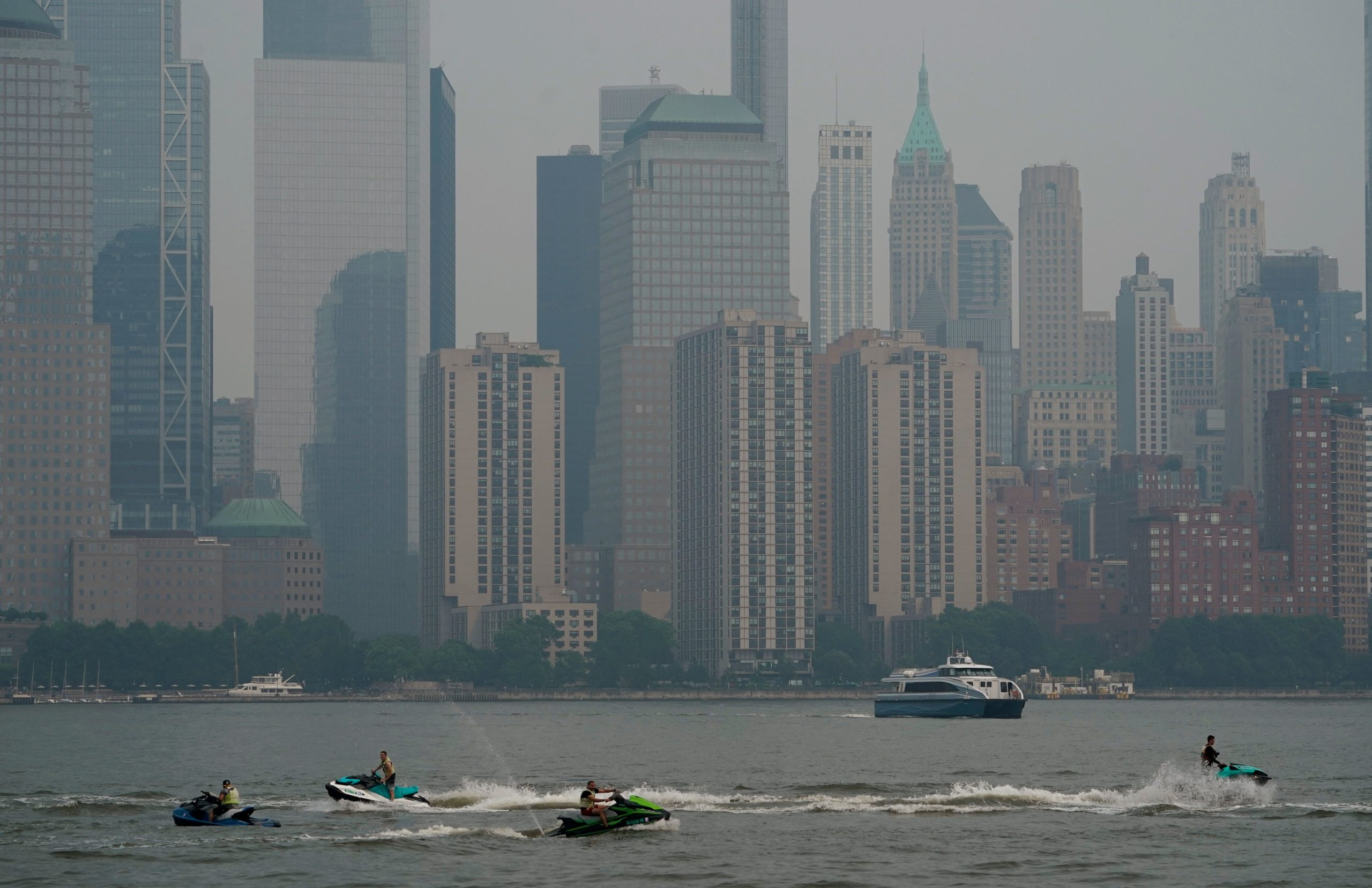 People ride jet skis near lower Manhattan on the Hudson River, July 20, 2021 as NY officials issue a air quality health advisory due to the west coast wildfires. (Photo by TIMOTHY A. CLARY/AFP via Getty Images)