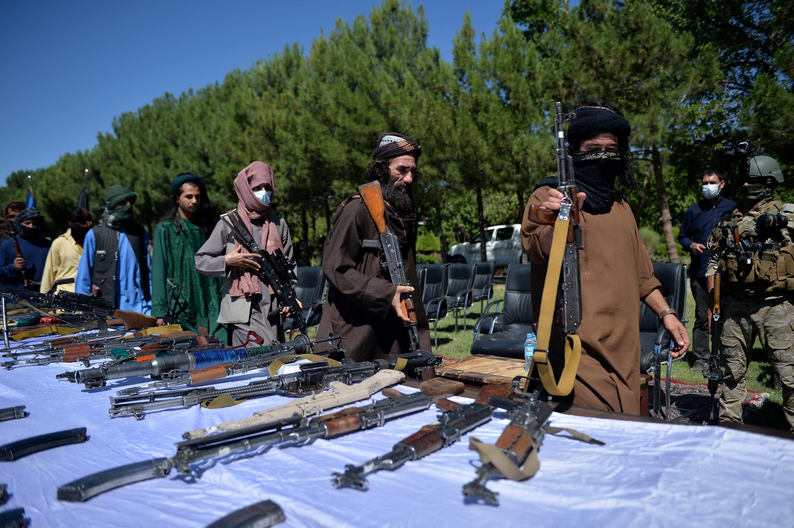 Taliban fighters put down their weapons as they surrendered to join the Afghanistan government during a ceremony in Herat on 24, 2021. (Photo by HOSHANG HASHIMIAFP via Getty Images)