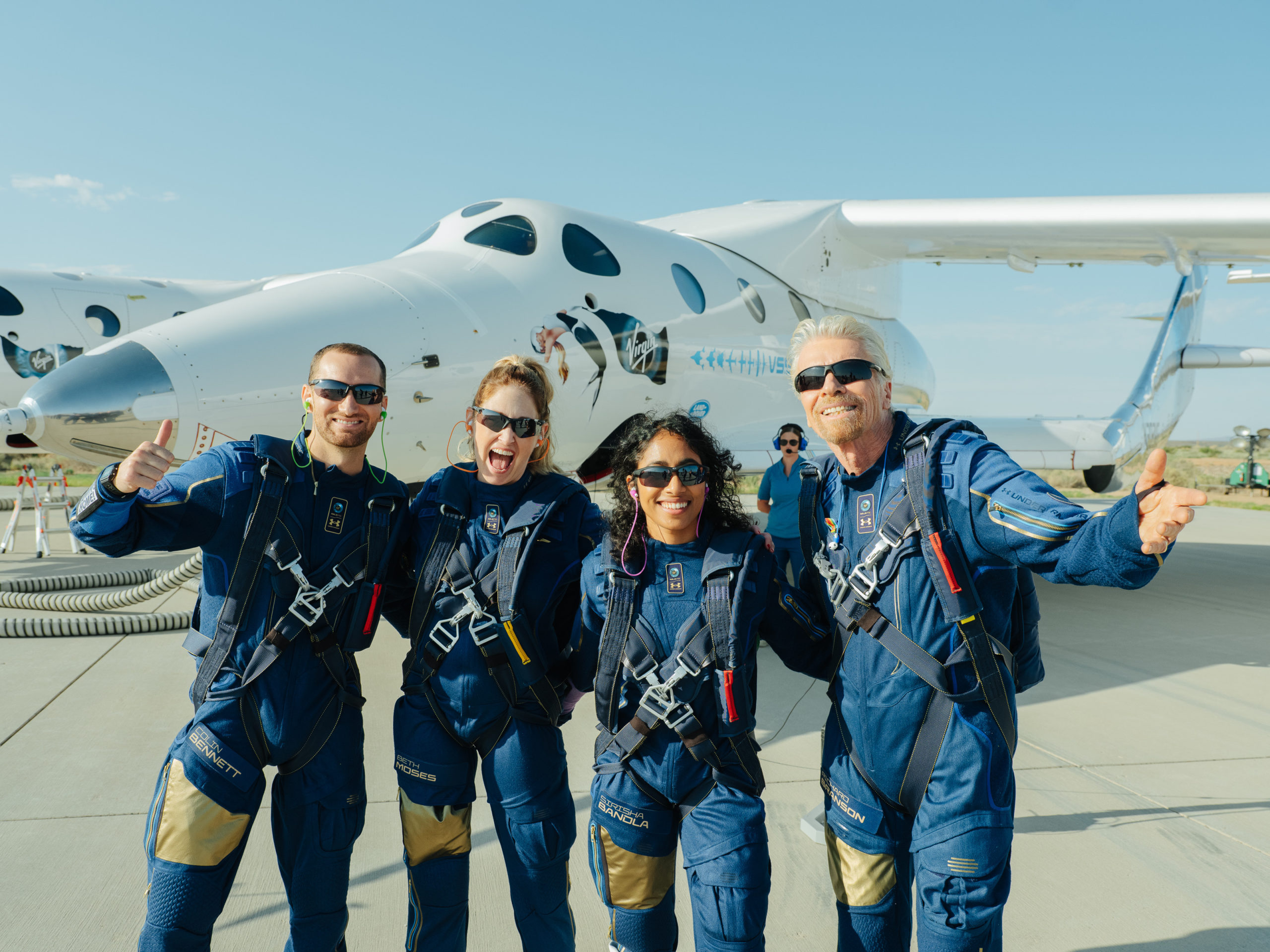 Richard Branson poses with three Virgin Galactic employees in front of the VSS Unity before flying to space on Sunday. (Virgin Galactic)