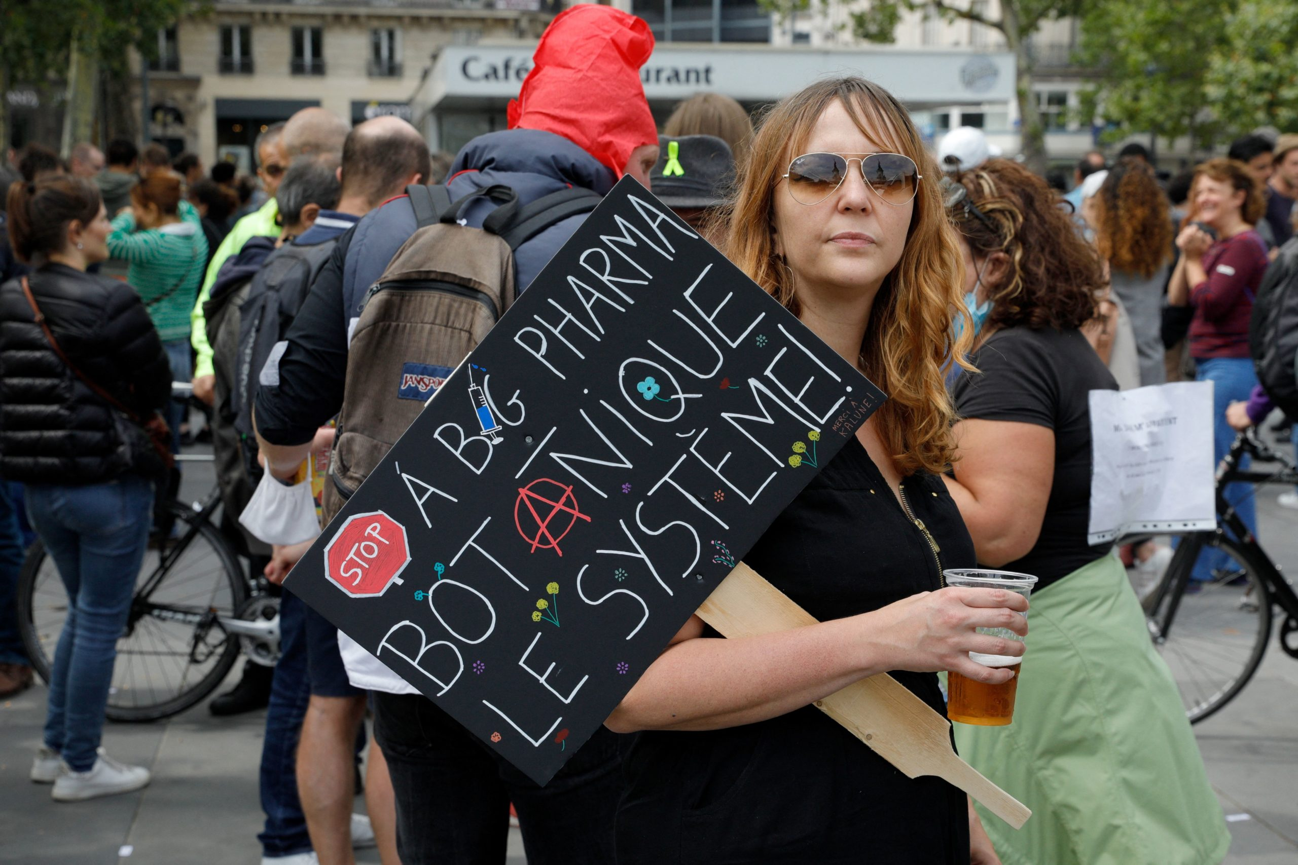 A woman holds a placard hostile to Pharmaceutical firms as she takes part in a gathering at Republic square in Paris on July 14, 2021 to protest against a governmental decision to impose Covid-19 tests for unvaccinated people who want to eat in restaurants or take long-distance trips, as the country looks to avoid a surge in more contagious Delta cases. French President announced the tougher measures on July 12, including mandatory vaccinations for healthcare and retirement home workers, prompting a surge in bookings for the jab. But critics accused the president of discriminating against sceptics or those who will not be fully vaccinated before the