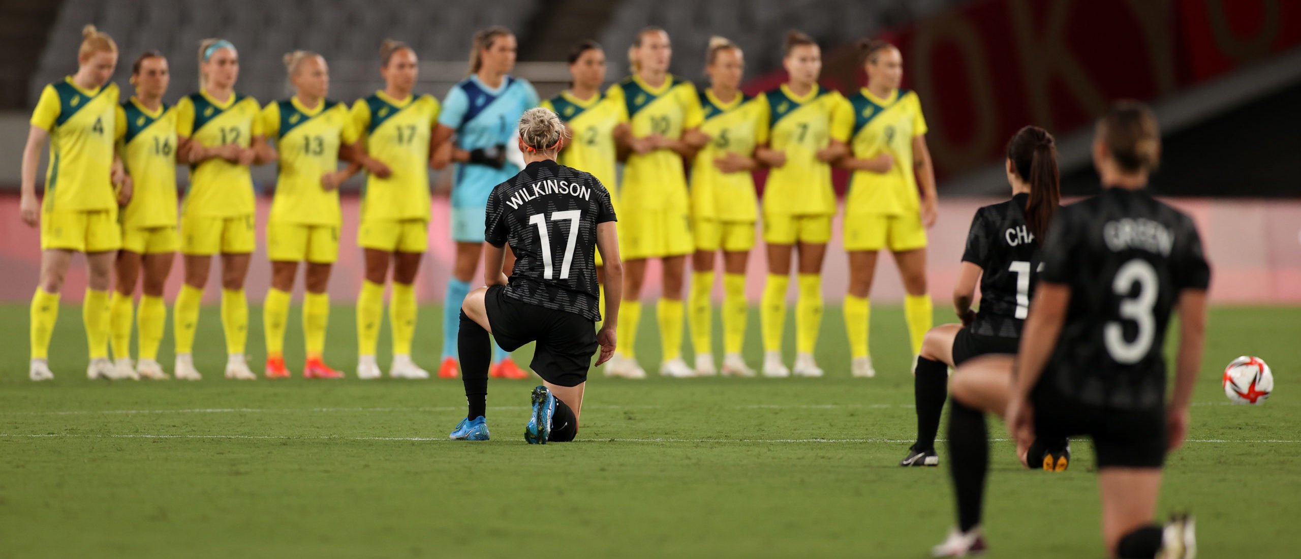 Team New Zealand takes a knee in support of the Black Lives Matter movement as players of Team Australia stand prior to the Women's First Round Group G match between Australia and New Zealand during the Tokyo 2020 Olympic Games at Tokyo Stadium on July 21, 2021 in Chofu, Tokyo, Japan. (Photo by Dan Mullan/Getty Images)