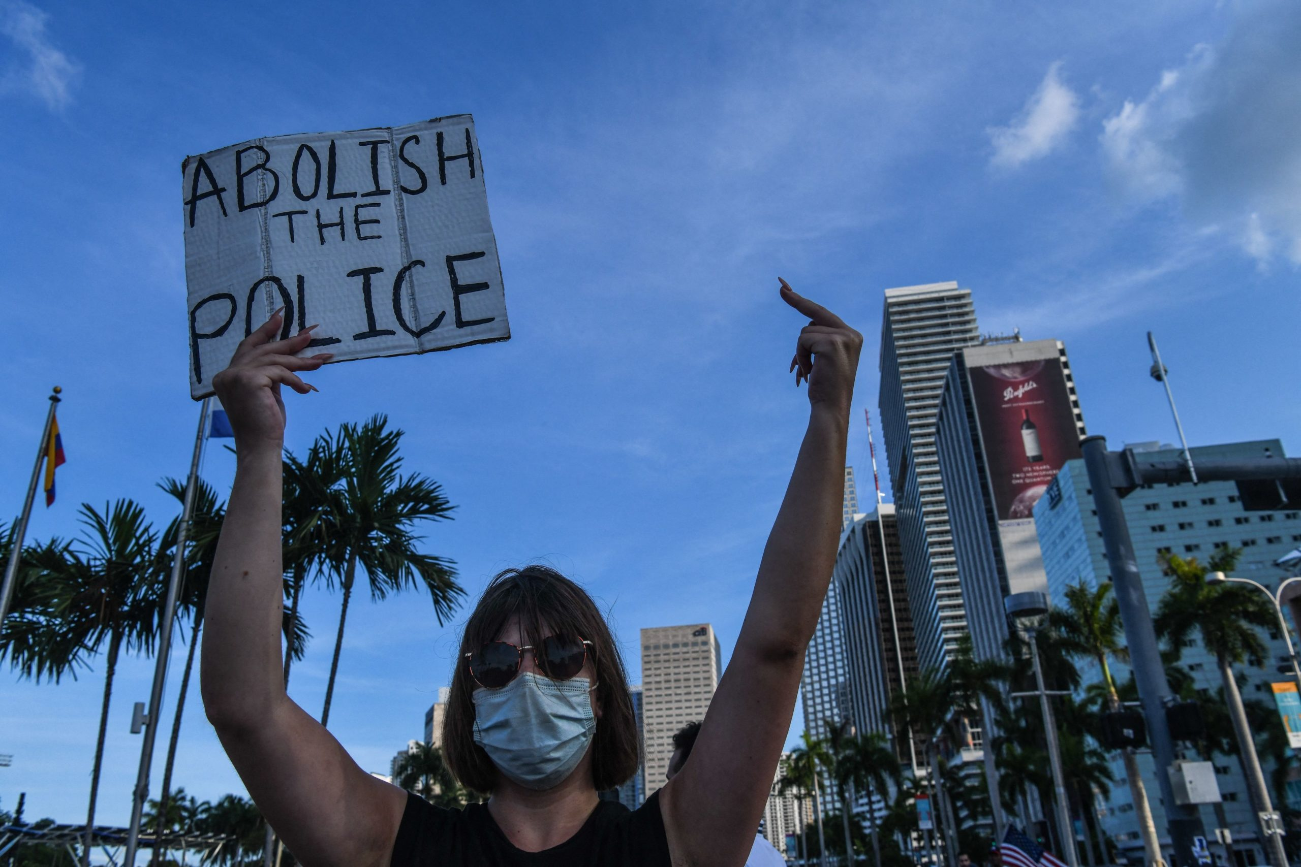 """A woman makes a rude gesture while holding a """"Abolish the Police"""" sign. Photo by CHANDAN KHANNA/AFP via Getty Images)"""