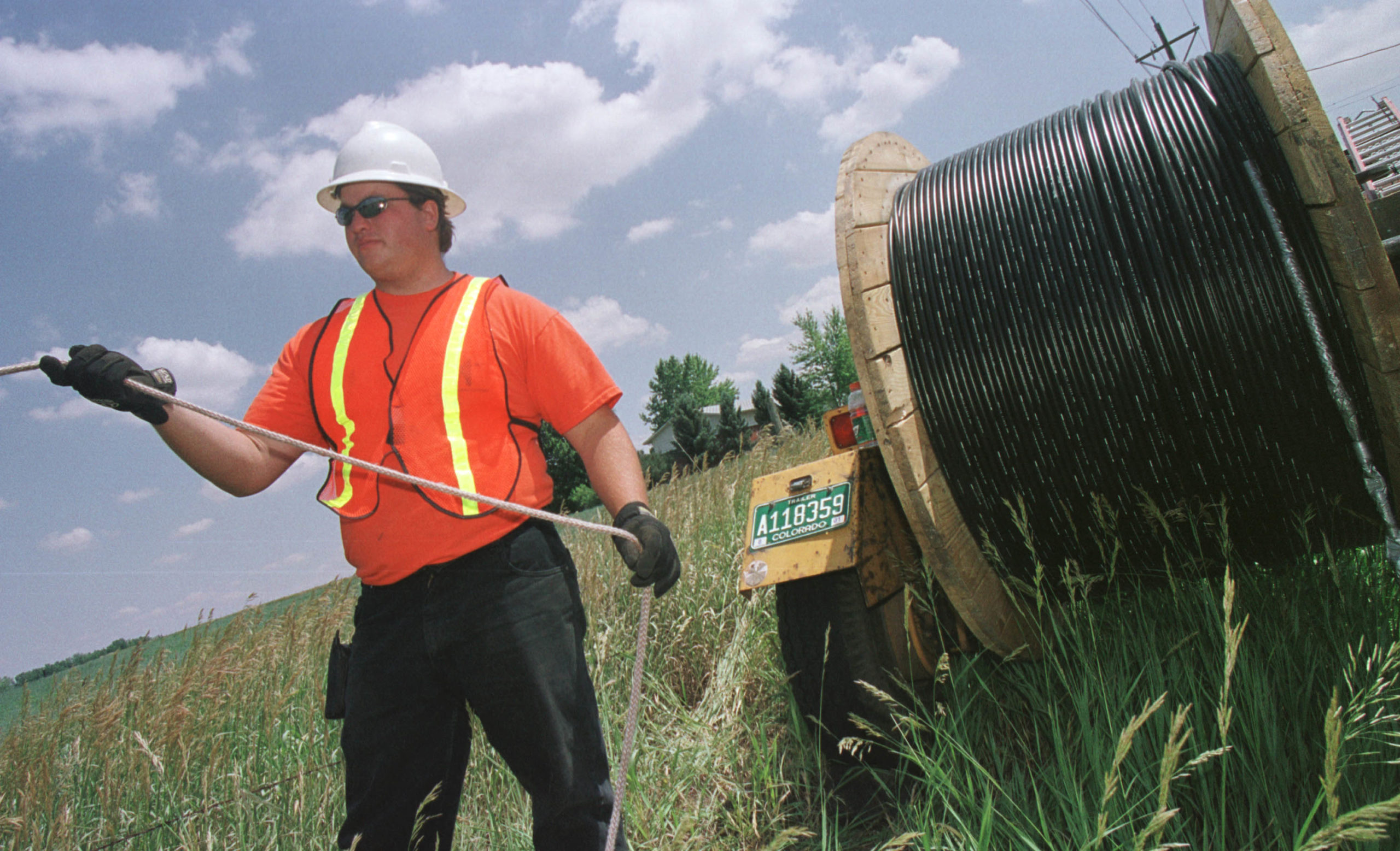 Reeltender Mo Laussie watches fiber-optic cable as he helps install the cable unto telephone poles in Louisville, CO. (Photo by Michael Smith/Getty Images)
