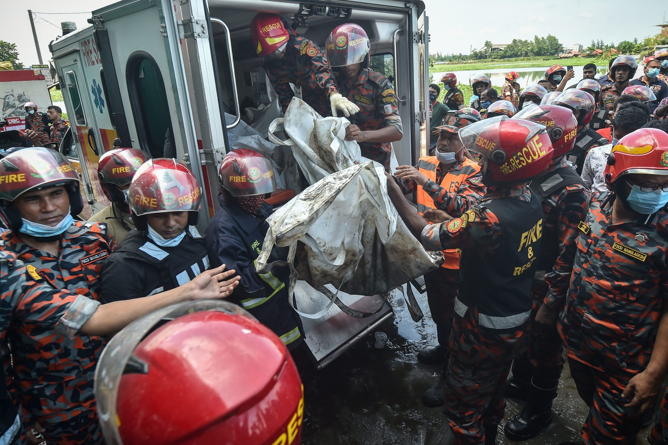 Firefighters and rescue workers recover bodies of the deceased who died in the fire. (Photo by MUNIR UZ ZAMAN/AFP via Getty Images)