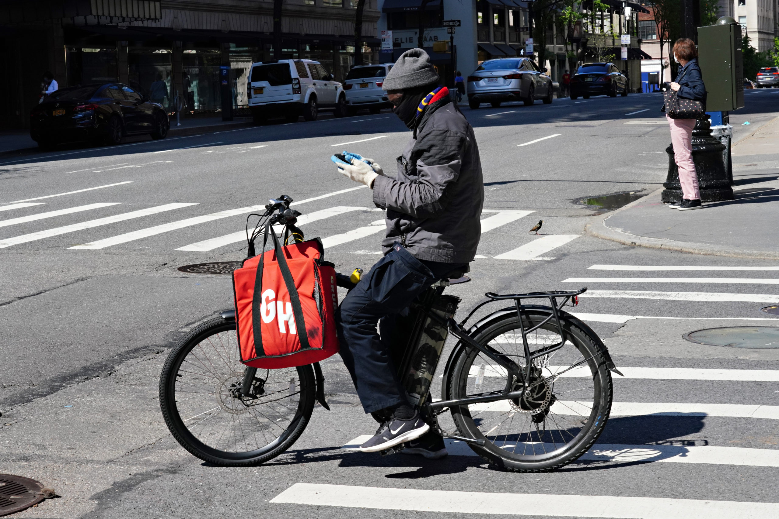 A Grubhub delivery person checks his phone during the coronavirus pandemic on May 3, 2020 in New York City. (Photo by Cindy Ord/Getty Images)