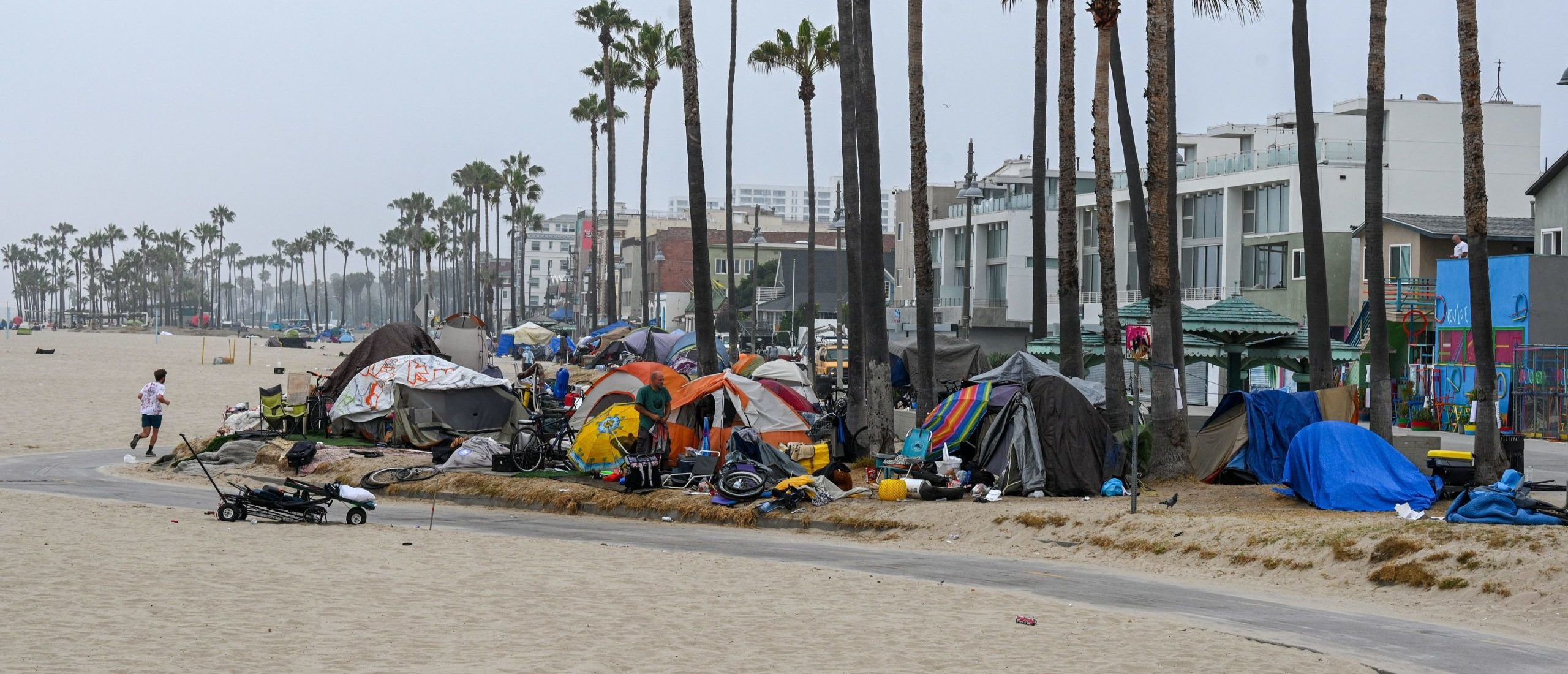 A man jogs along the beach as authorities prepare to begin clearing homeless encampments at the Venice Beach Boardwalk ahead of the Independence Day holiday weekend, July 2, 2021 in Los Angeles, California. (Photo by ROBYN BECK/AFP via Getty Images)