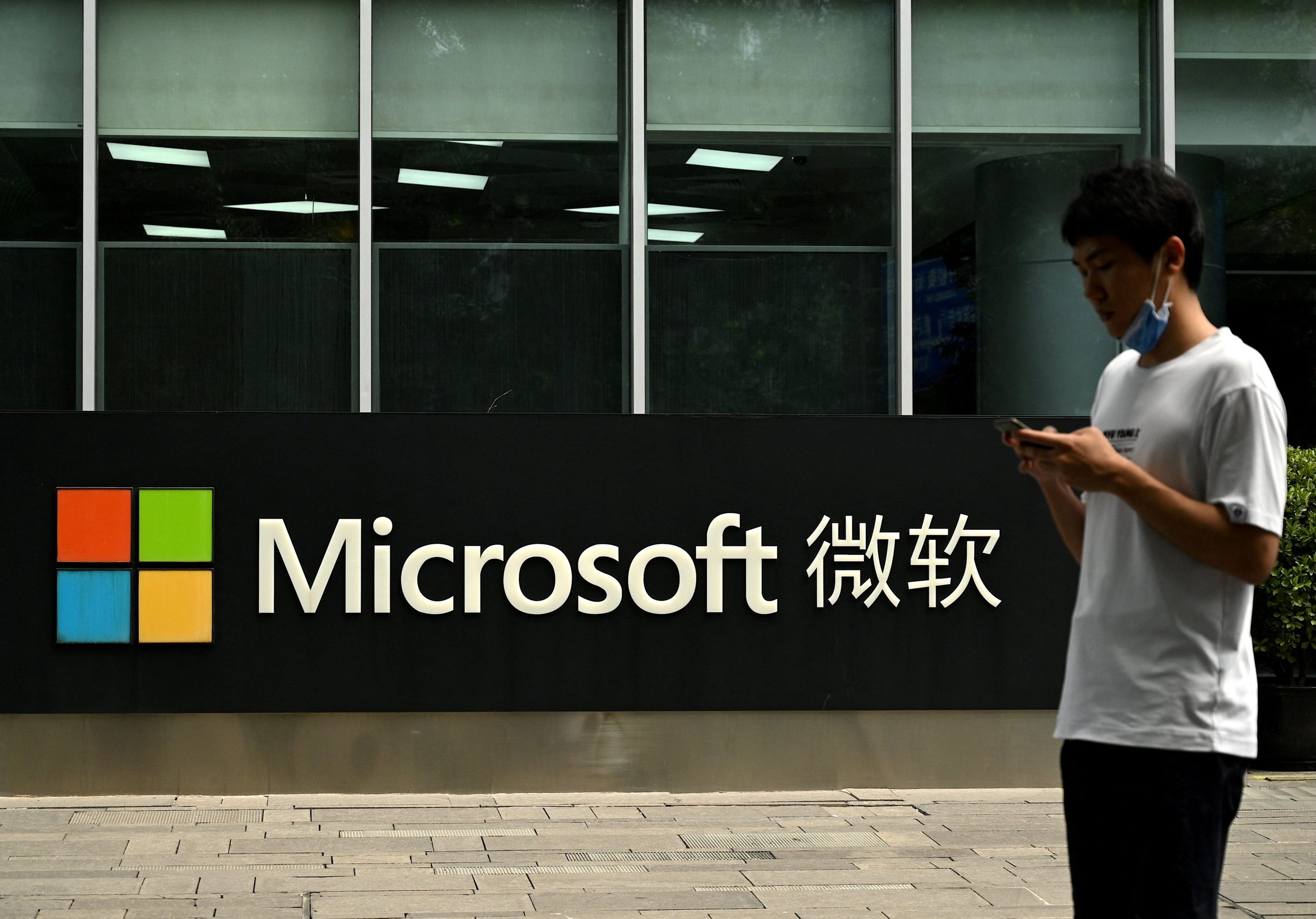 """A man looks at his phone while outside Microsoft's local headquarters in Beijing on July 20, 2021, the day after the US accused Beijing of carrying out the cyber attack on Microsoft and charged four Chinese nationals over the """"malicious"""" hack in March. (Photo by NOEL CELIS/AFP via Getty Images)"""