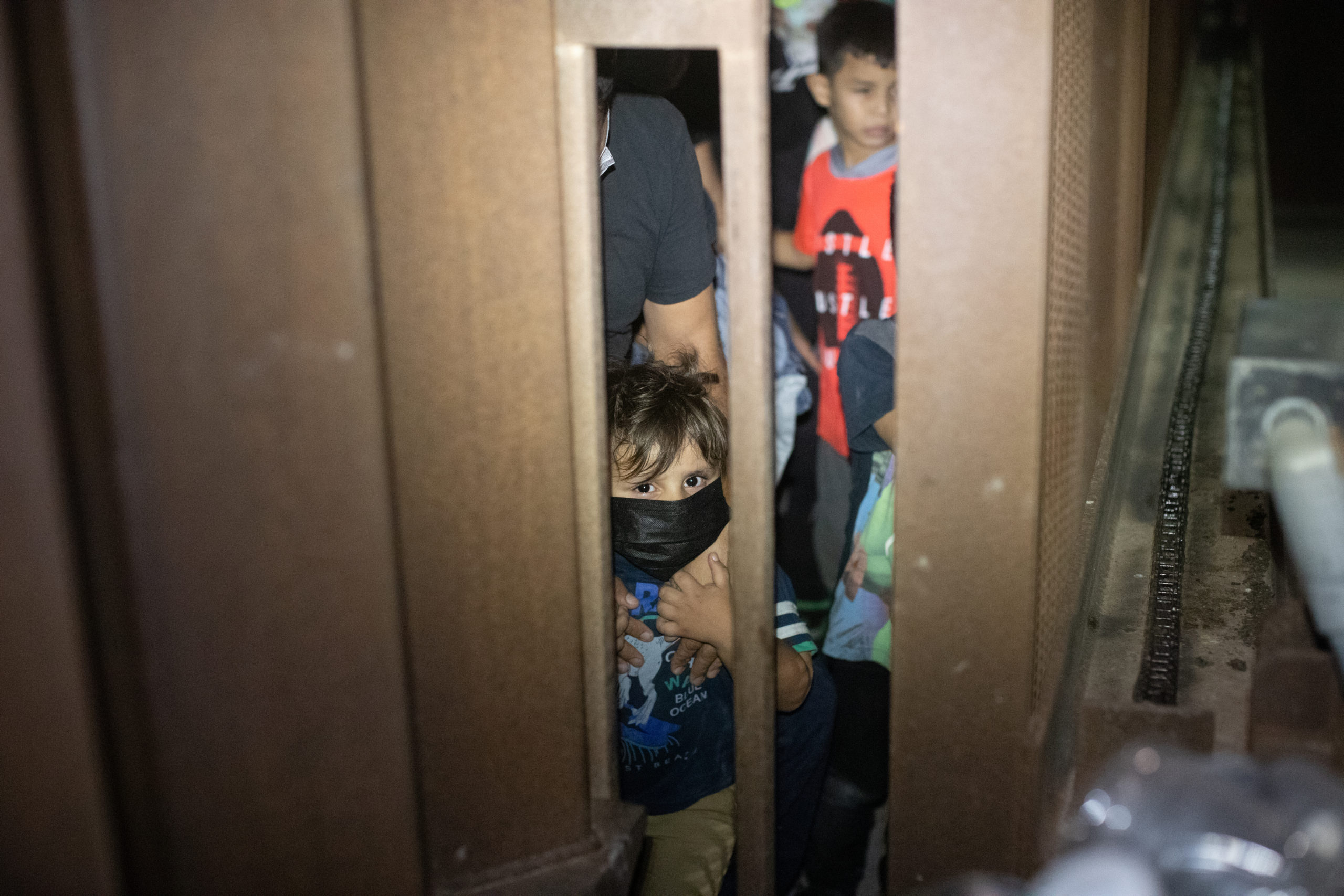 Groups of migrants waited on the other side of the border wall after illegally entering the U.S. near the Hidalgo Point of Entry in Hidalgo, Texas, on August 10, 2021. (Kaylee Greenlee - Daily Caller News Foundation)