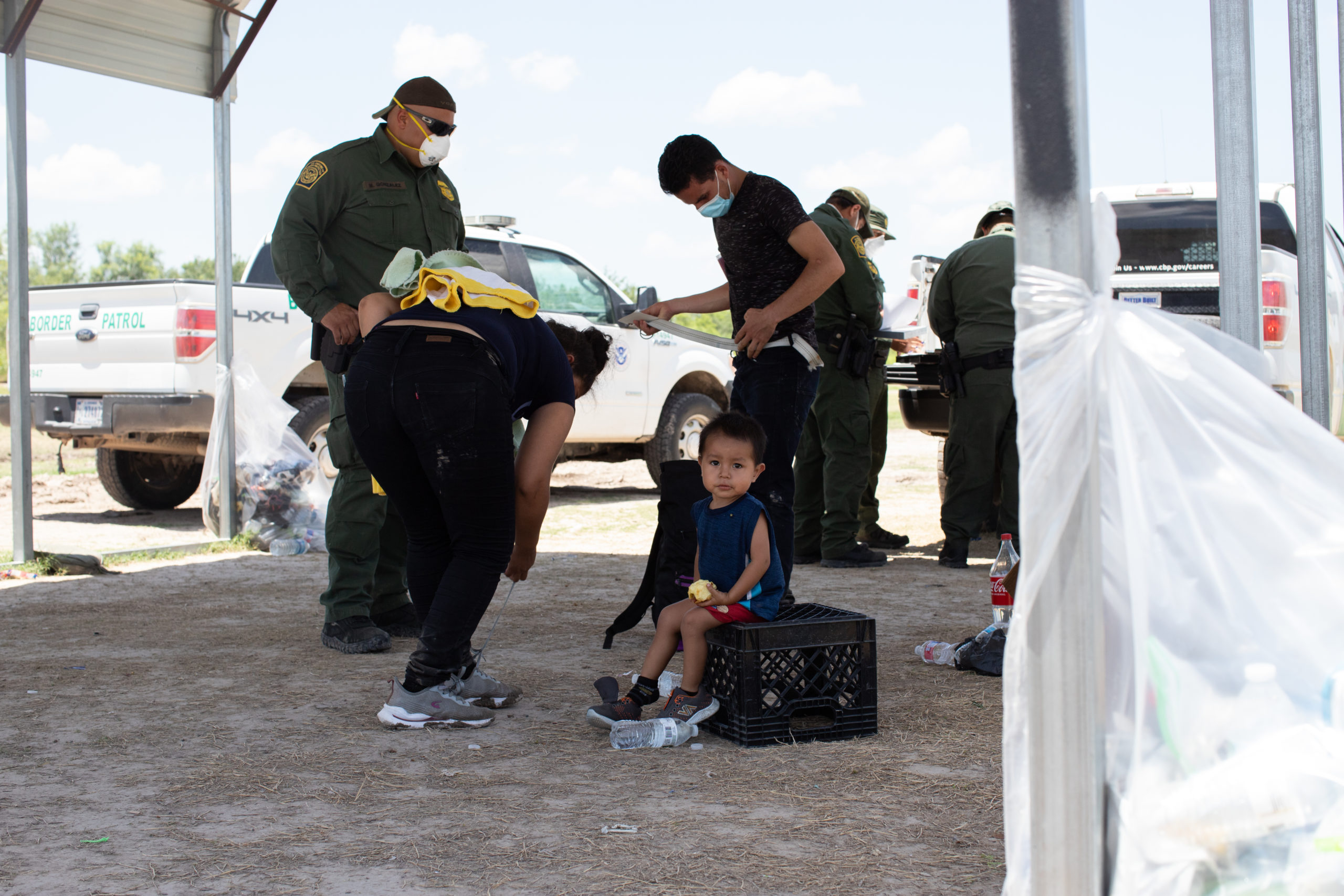 A migrant boy and his mother go through routine field processing after illegally entering the U.S. near La Joya, Texas, on August 7, 2021. (Kaylee Greenlee - Daily Caller News Foundation)