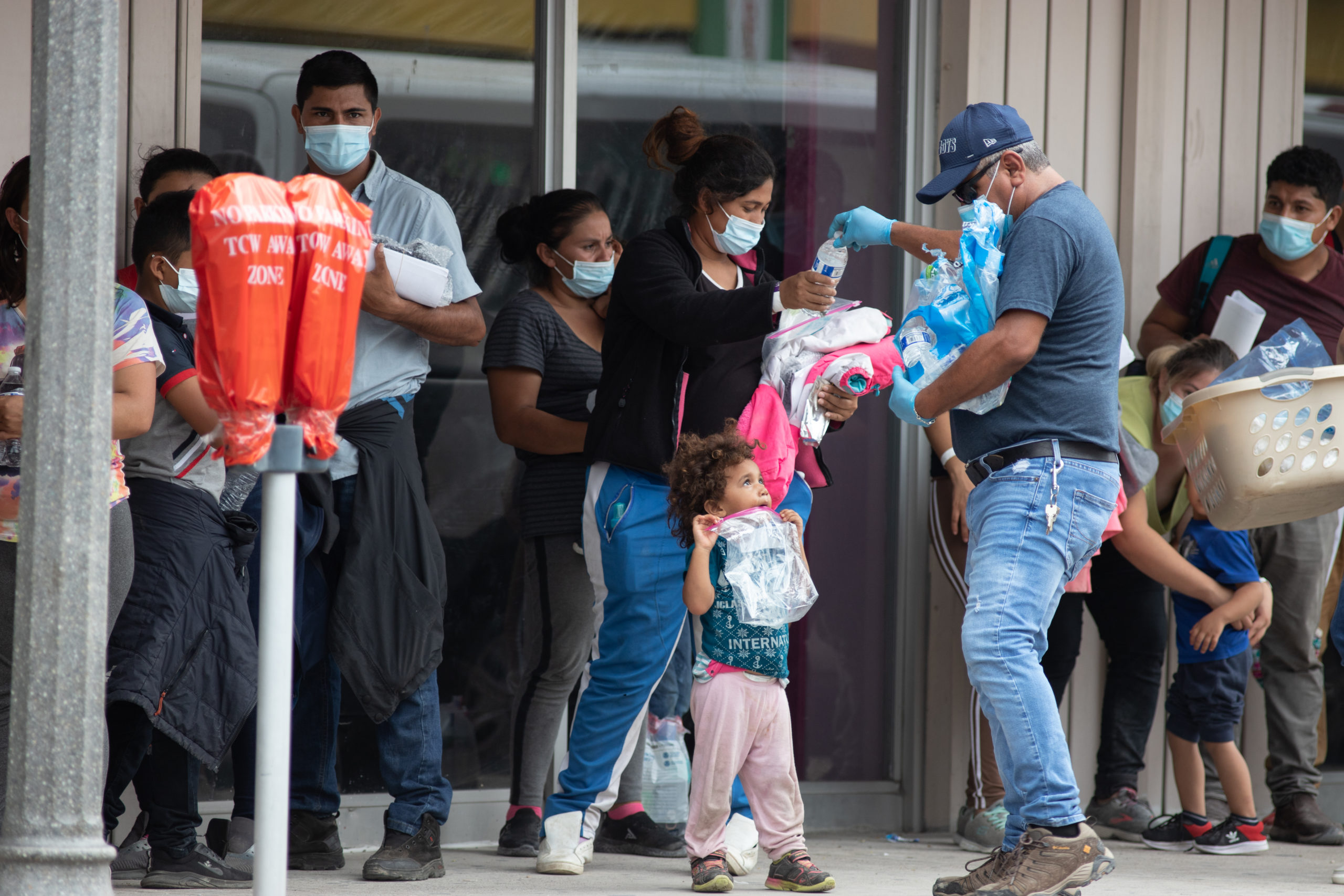 A group of at least 100 migrants waited outside a COVID-19 testing center after being released from federal custody in downtown McAllen, Texas, on August 6, 2021. (Kaylee Greenlee - Daily Caller News Foundation)