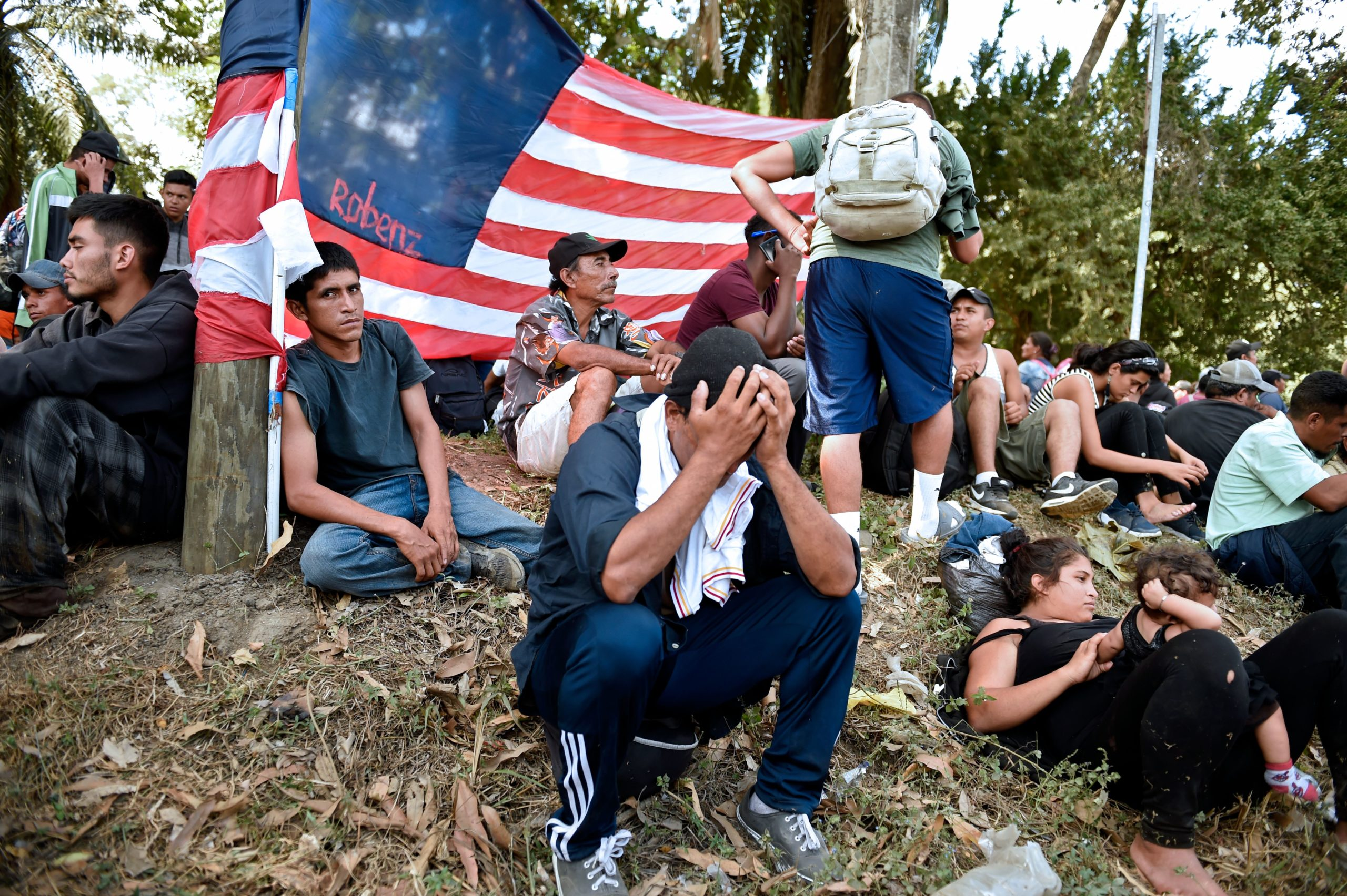 Central American migrants - mostly Hondurans heading in a caravan to the US - rest next to a US flag on their way from Ciudad Hidalgo to Tapachula, Chiapas State, Mexico, on January 23, 2020. (Photo by ALFREDO ESTRELLA/AFP via Getty Images)