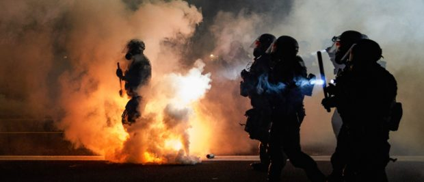 TOPSHOT - Oregon Police wearing anti-riot gear march towards protesters through tear gas smoke during the 100th day and night of protests against racism and police brutality in Portland, Oregon, on September 5, 2020. - Police arrested dozens of people and used tear gas against hundreds of demonstrators in Portland late on September 5 as the western US city marked 100 days since Black Lives Matter protests erupted against racism and police brutality. Protests in major US cities erupted after the death of African American George Floyd in May 2020 at the hands of a white police officer in Minneapolis. (Photo by Allison Dinner / AFP) (Photo by ALLISON DINNER/AFP via Getty Images)