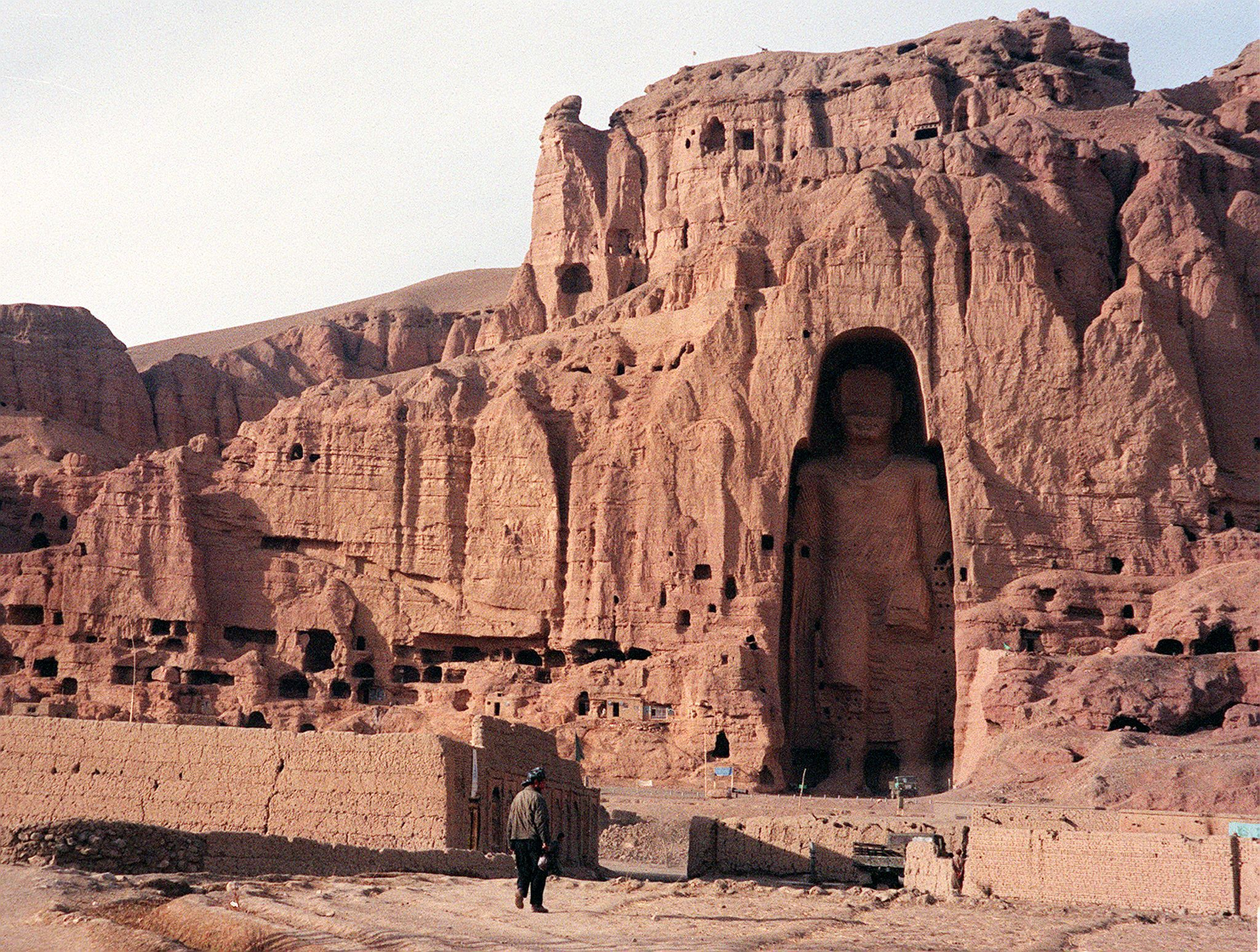 (FILES) A file photo dated 07 December 1997 shows an Afghan walking near the world's tallest standing statue of Buddha in Bamiyan province of Afghanistan. In a report in Hong Kong, 16 May 2002, a Taiwan-based Buddhist leader will donate one million Hong Kong dollars (129,000 USD) to help restore the giant Buddha statues destroyed by the Taliban. (FILM) AFP PHOTO/ Jean-Claude CHAPON (Photo by JEAN-CLAUDE CHAPON / AFP) (Photo by JEAN-CLAUDE CHAPON/AFP via Getty Images)