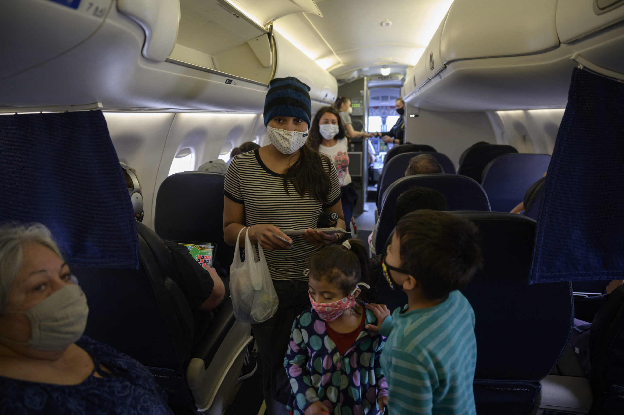 Reina (C L), Diana (C) and Dariel (R) from El Salvador board a flight on March 30, 2021 from Houston to New York, following their release from a US government holding facility for illegal migrants seeking asylum in McAllen, Texas. Photo by ED JONES/AFP via Getty Images)