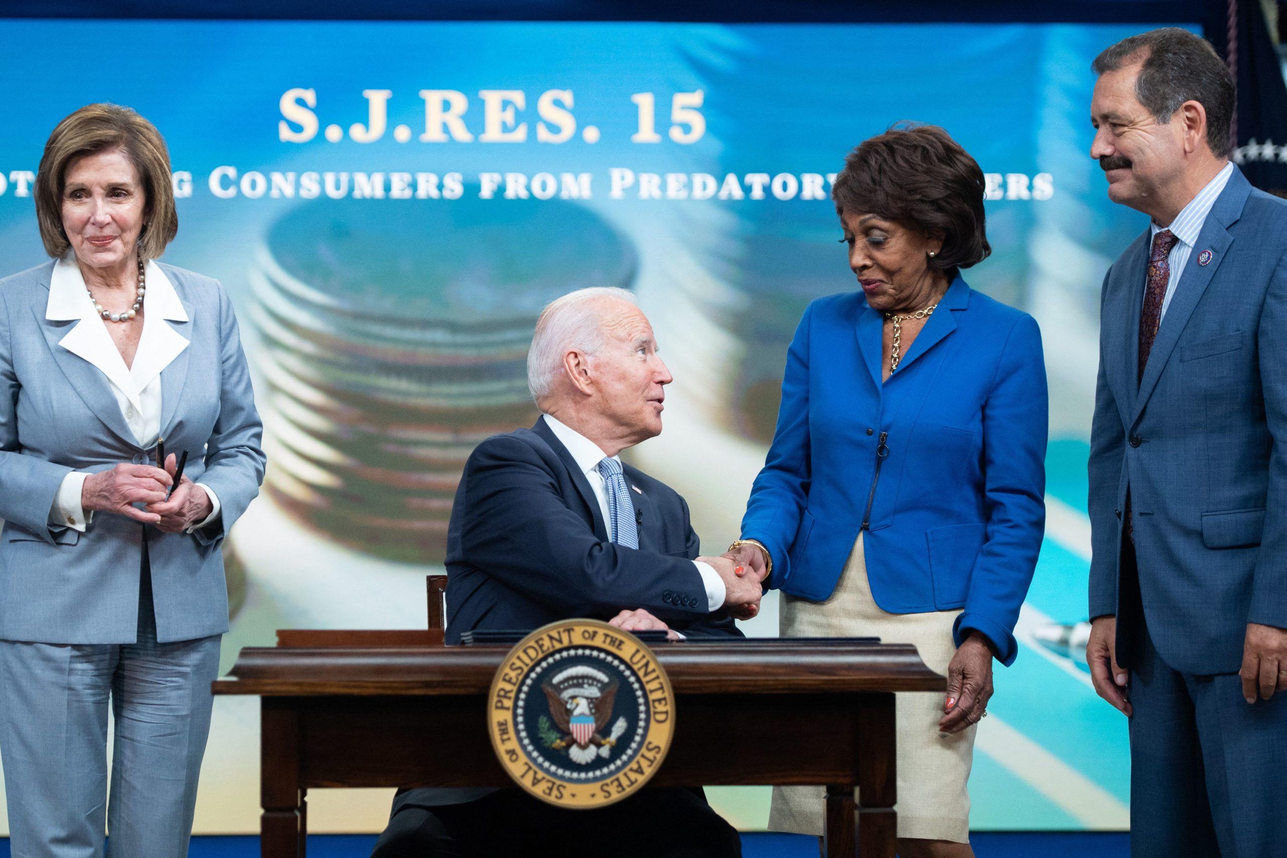 President Joe Biden sits alongside Speaker of the House Nancy Pelosi and Financial Services Chairwoman Maxine Waters on June 30. (Saul Loeb/AFP via Getty Images)