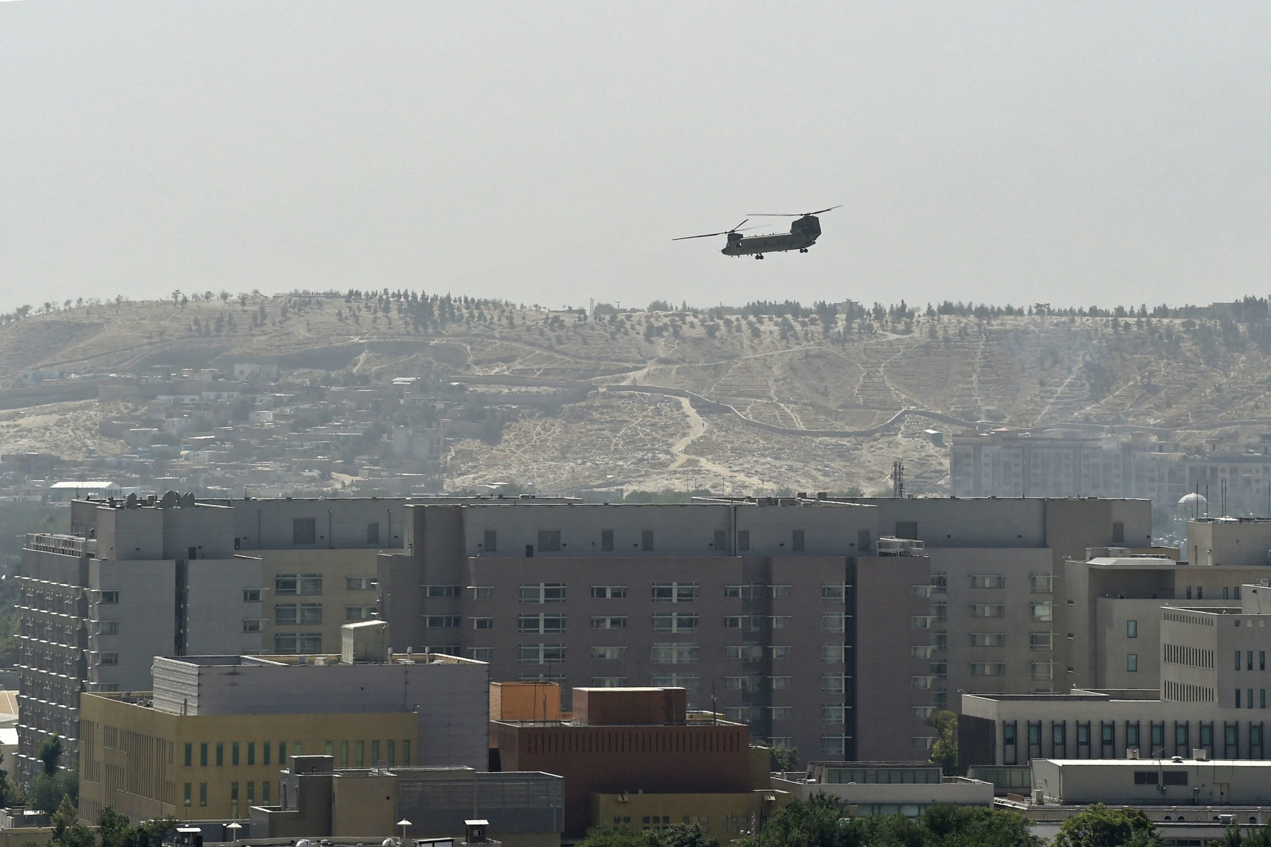 TOPSHOT - A U.S. Chinook military helicopter flies above the US embassy in Kabul on August 15, 2021. Several hundred employees of the US embassy in Kabul have been evacuated from Afghanistan, a US defense official said on August 15, 2021, as the Taliban entered the capital. (Photo by Wakil KOHSAR / AFP) (Photo by WAKIL KOHSAR/AFP via Getty Images)