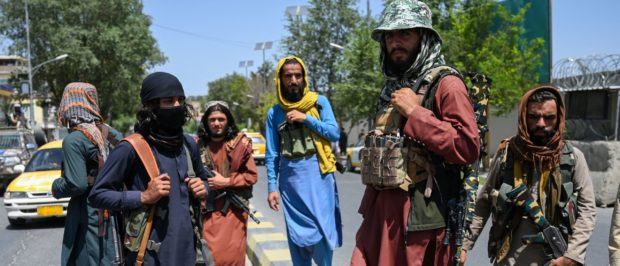 Taliban fighters stand guard along a street near the Zanbaq Square in Kabul on August 16, 2021, after a stunningly swift end to Afghanistan's 20-year war, as thousands of people mobbed the city's airport trying to flee the group's feared hardline brand of Islamist rule. (Photo by Wakil Kohsar / AFP) (Photo by WAKIL KOHSAR/AFP via Getty Images)