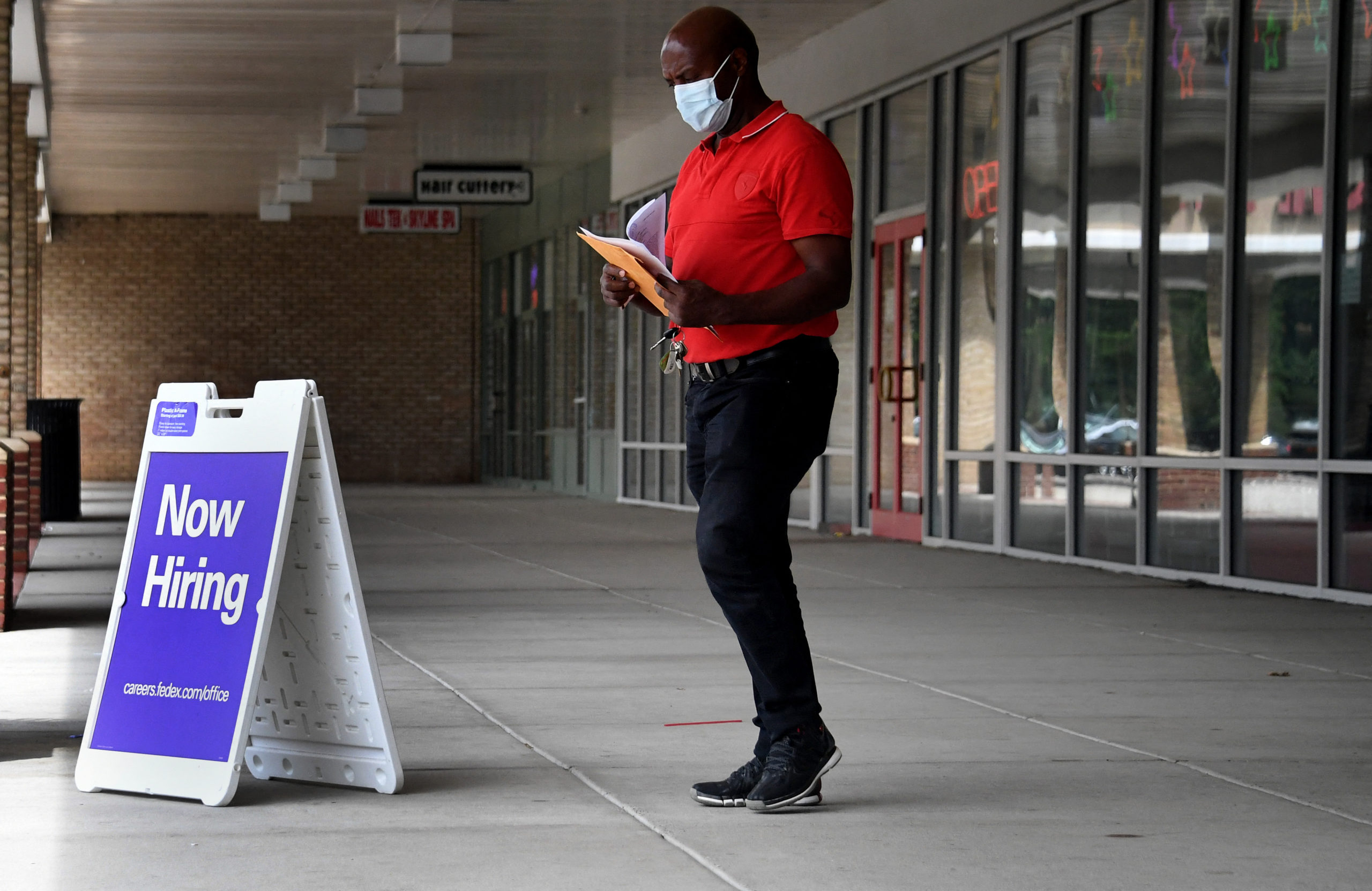 """Pedestrians walk by a """"Now Hiring"""" sign outside a store on Aug. 16 in Arlington, Virginia. (Olivier Douliery/AFP via Getty Images)"""