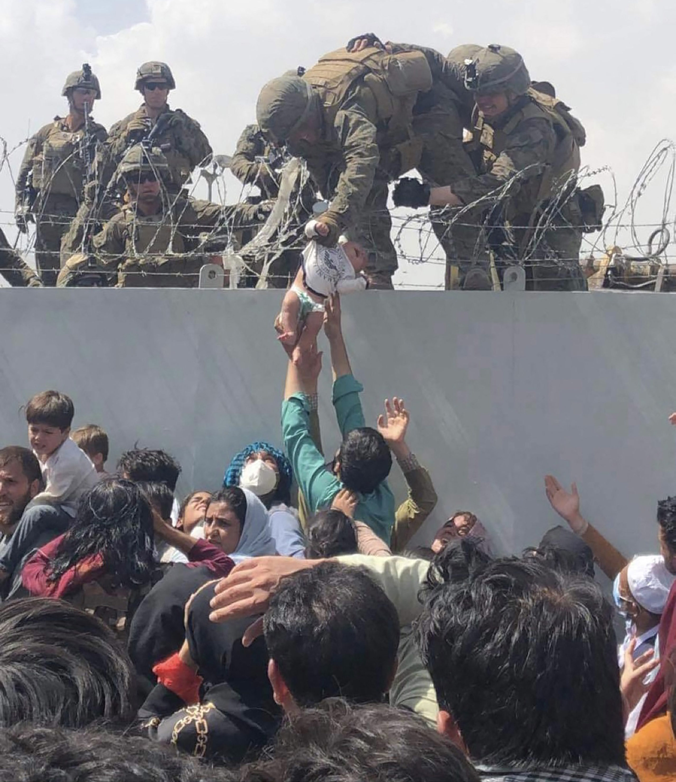 """TOPSHOT - This image made available to AFP on August 20, 2021 by Omar Haidiri, shows a US Marine grabbing an infant over a fence of barbed wire during an evacuation at Hamid Karzai International Airport in Kabul on August 19, 2021. - A Pentagon official confirmed Friday that US evacuation operations from Kabul's airport have been stalling because the receiving base in Qatar is overflowing and could not receive evacuees. """"There has been a considerable amount of time today where there haven't been departures,"""" Brigadier General Dan DeVoe of the US Air Mobility Command told reporters. (Photo by Omar HAIDIRI / Courtesy of Omar Haidiri / AFP) (Photo by OMAR HAIDIRI/Courtesy of Omar Haidiri/AFP via Getty Images)"""