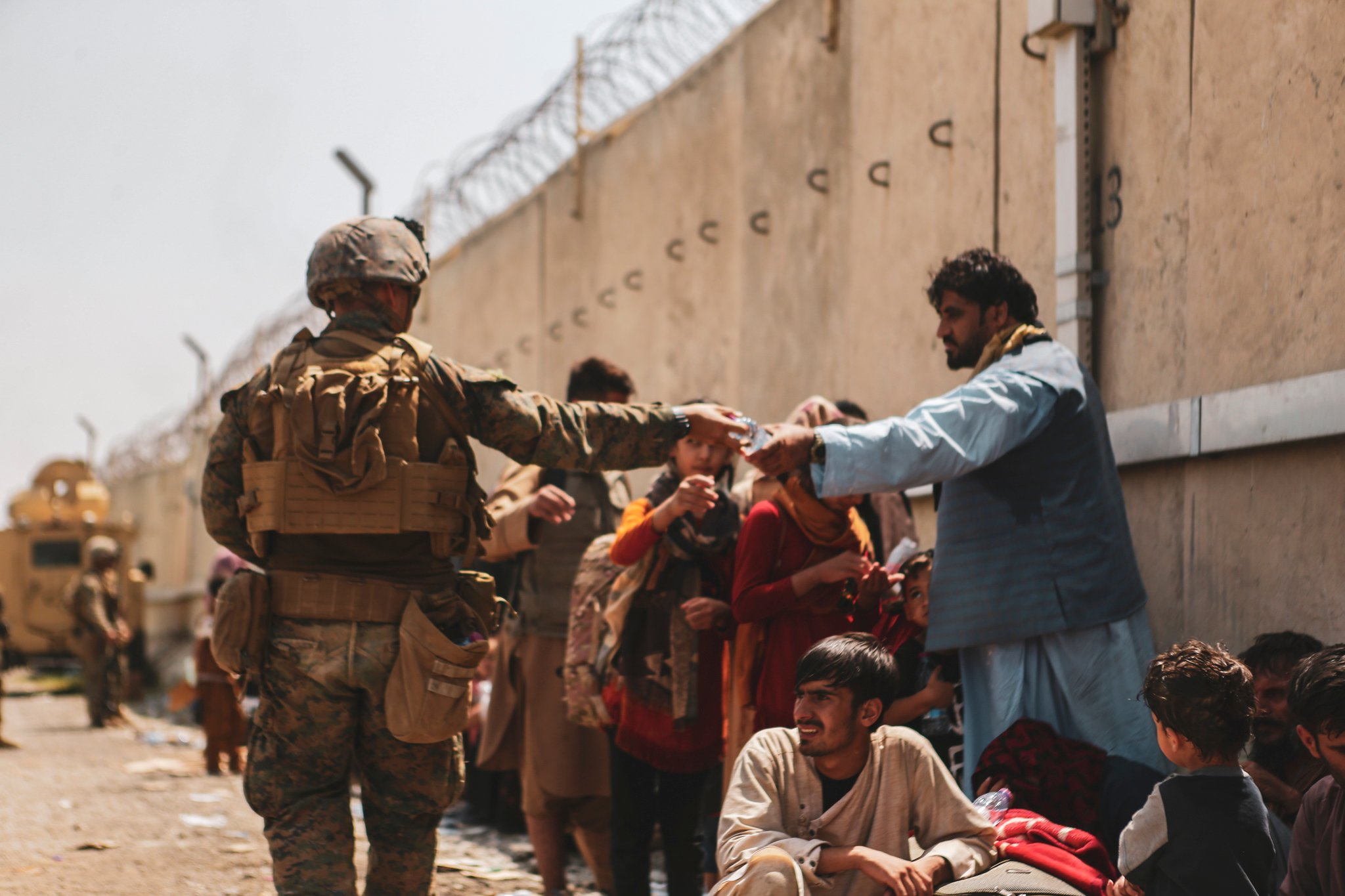 KABUL, AFGHANISTAN - AUGUST 21: In this handout provided by the U.S. Marine Corps, a Marine with the 24th Marine Expeditionary unit (MEU) passes out water to evacuees during the evacuation at Hamid Karzai International Airport during the evacuation on August 21, 2021 in Kabul, Afghanistan. The U.S. military is assisting in the evacuation effort. (Photo by Isaiah Campbell/U.S. Marine Corps via Getty Images)