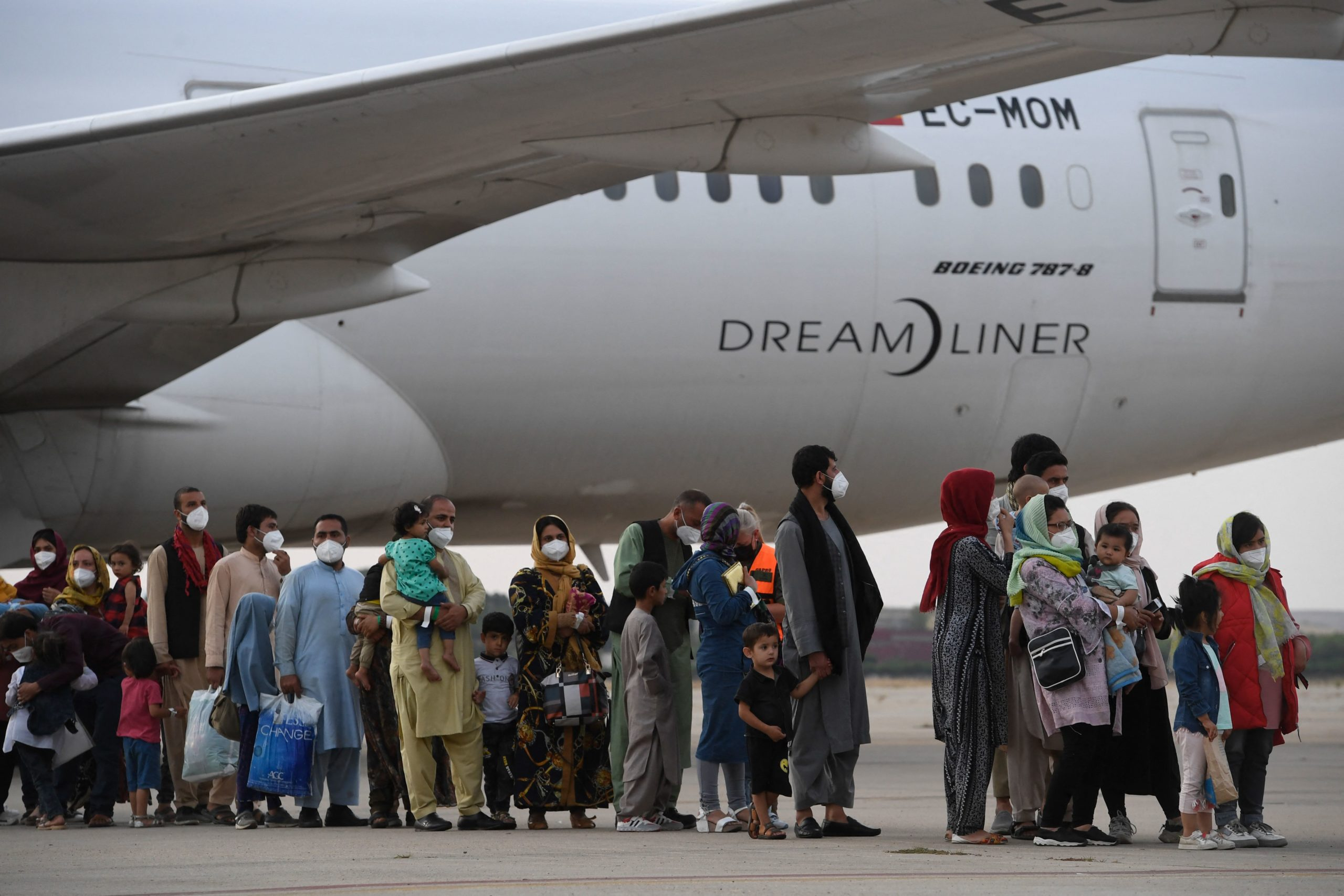 Refugees queue on the tarmac after disembarking from an evacuation flight from Kabul, at the Torrejon de Ardoz air base, 30 km from Madrid, on August 24, 2021. - Spain has been evacuating its nationals and local contractors from Afghanistan via Dubai since the Taliban swept to power ten days ago. Another 420 people are expected to arrive in Spain on August 24, 2021, including 290 people from Dubai and 130 who are expected to leave on a Spanish military plane from Kabul. (Photo by PIERRE-PHILIPPE MARCOU/AFP via Getty Images)