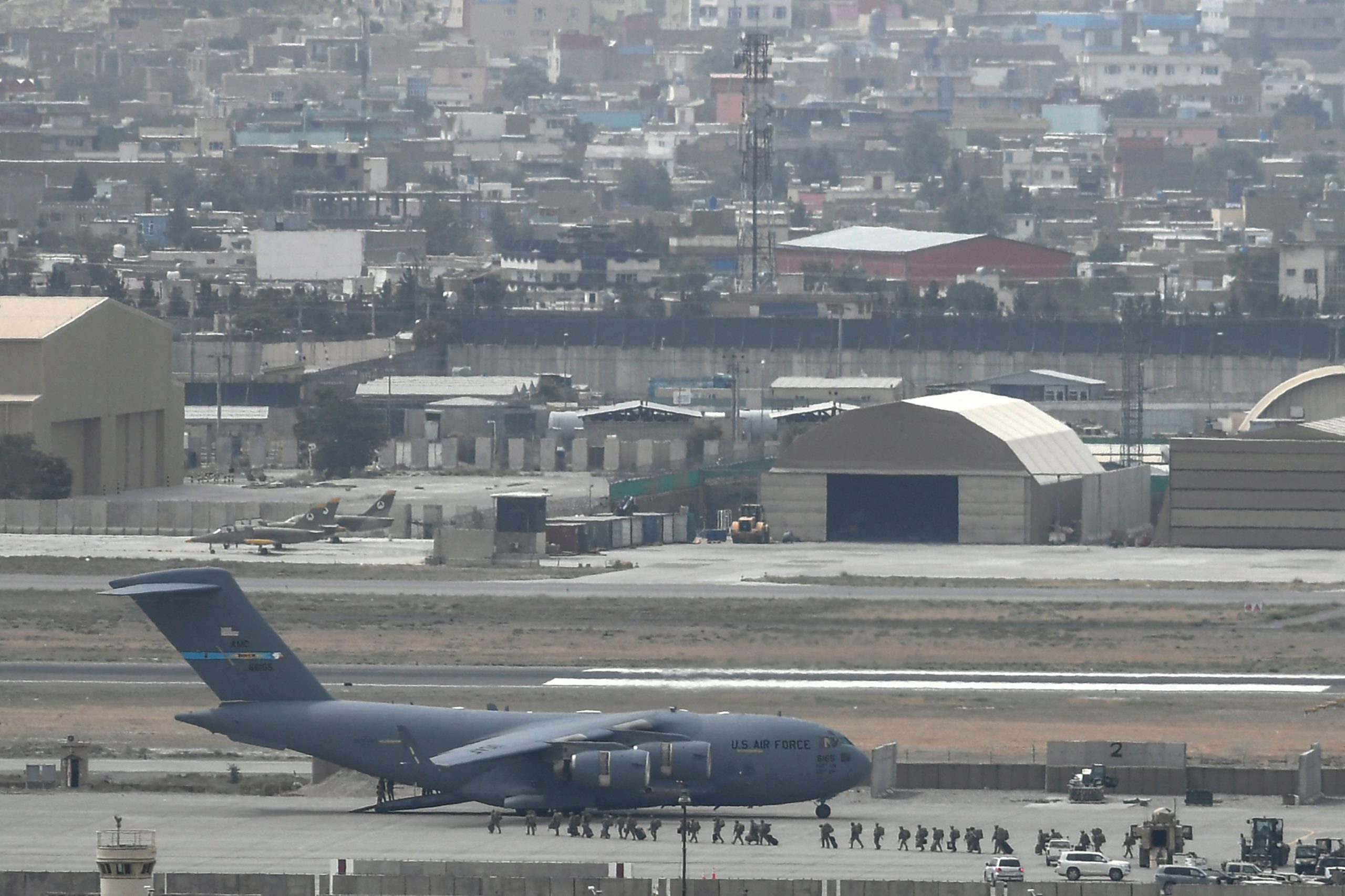 US soldiers arrive board an US Air Force aircraft at the airport in Kabul on August 30, 2021. - Rockets were fired at Kabul's airport on August 30 where US troops were racing to complete their withdrawal from Afghanistan and evacuate allies under the threat of Islamic State group attacks. (Photo by Aamir QURESHI / AFP) (Photo by AAMIR QURESHI/AFP via Getty Images)
