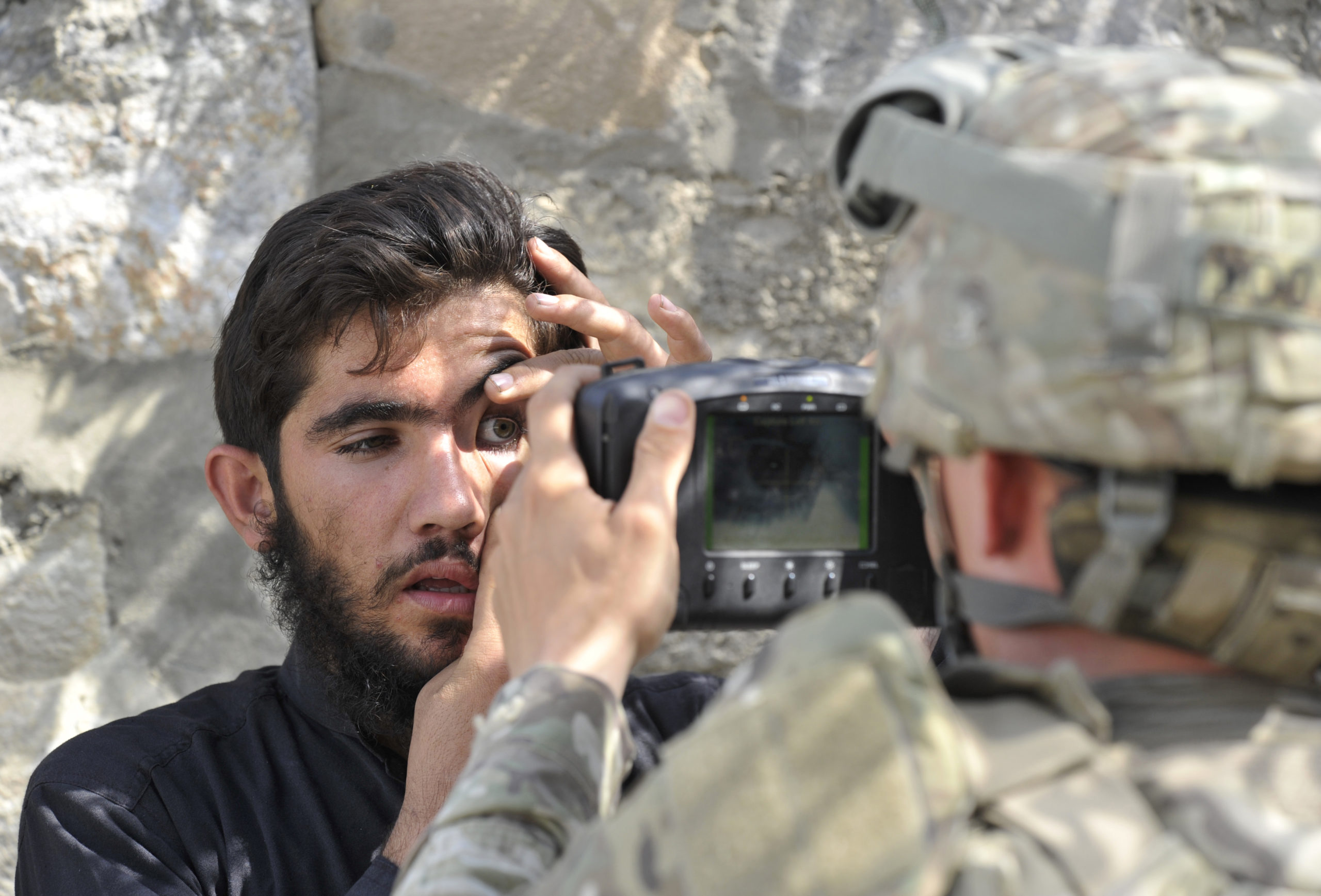 A US army soldier from The HHB 3-7 Field Artillery Regiment 3rd Bct 25th ID, scans the eyes of an Afghan resident with an Automated Biometric Identification System (ABIS) during a mission at Turkham on October 6, 2011, a border crossing town in the Nangarhar province of Afghanistan and the Khyber Agency of Pakistan's Federally Administered Tribal Areas. The new Afghan-Indian security pact could inflame Pakistan's proxy war against India and threatens Islamabad's regional ambitions in South Asia, as ties with Kabul and Washington hit rock bottom. Kabul claims the recent murder of its peace envoy Burhanuddin Rabbani was plotted in Pakistan, and has accused Islamabad of hindering the investigation. AFP PHOTO/TAUSEEF MUSTAFA (Photo credit should read TAUSEEF MUSTAFA/AFP via Getty Images)