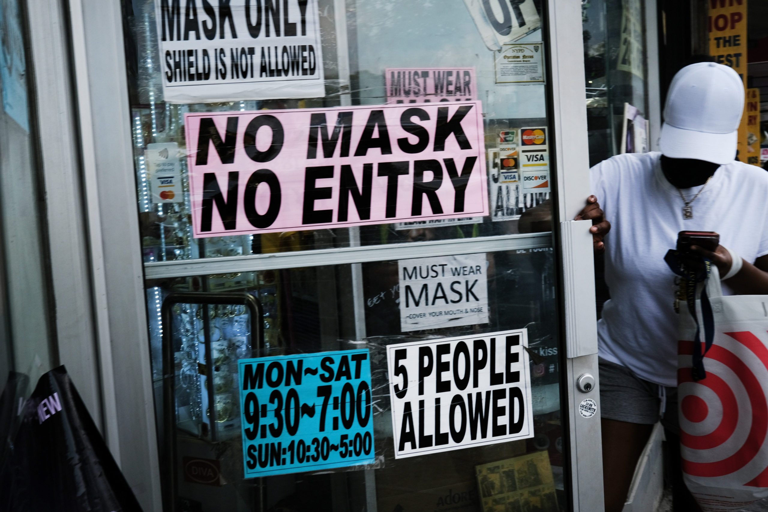 People walk out of a store requesting that people wear masks on July 26 in New York City. (Spencer Platt/Getty Images)