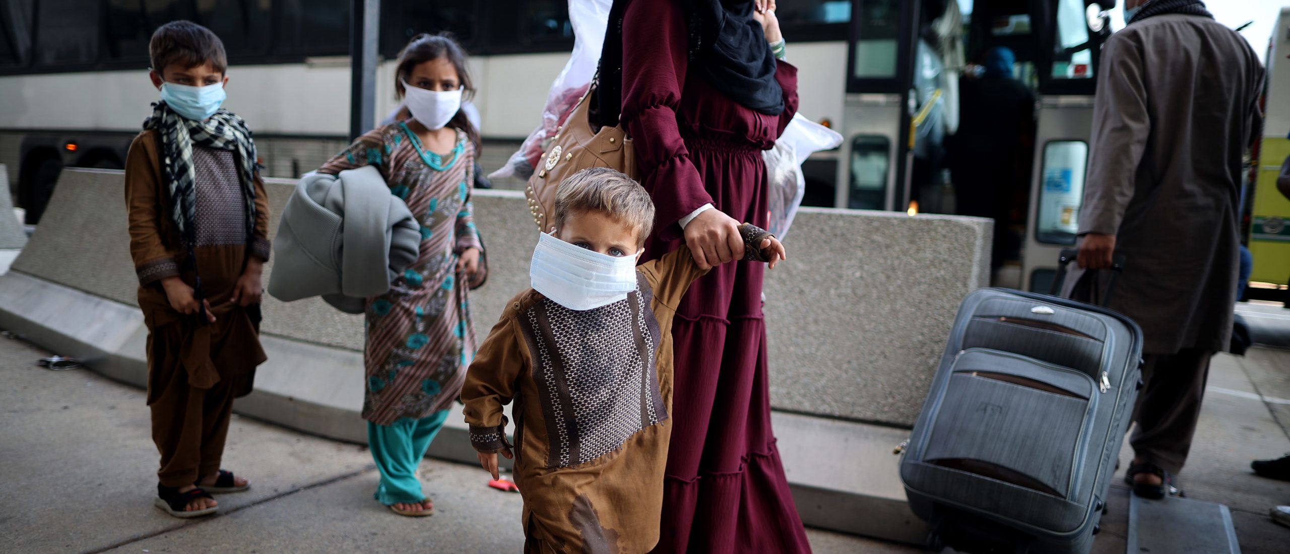 """DULLES, VIRGINIA - AUGUST 27: Refugees board buses that will take them to a processing center at Dulles International Airport after being evacuated from Kabul following the Taliban takeover of Afghanistan August 27, 2021 in Dulles, Virginia. Refugees continued to arrive in the United States one day after twin suicide bombings at the gates of the airport in Kabul killed 13 U.S. military service members and nearly 100 Afghans. """"We will not forgive,"""" President Joe Biden warned ISIS, who claimed responsibility for the attacks. """"We will not forget. We will hunt you down and make you pay."""" (Photo by Chip Somodevilla/Getty Images)"""