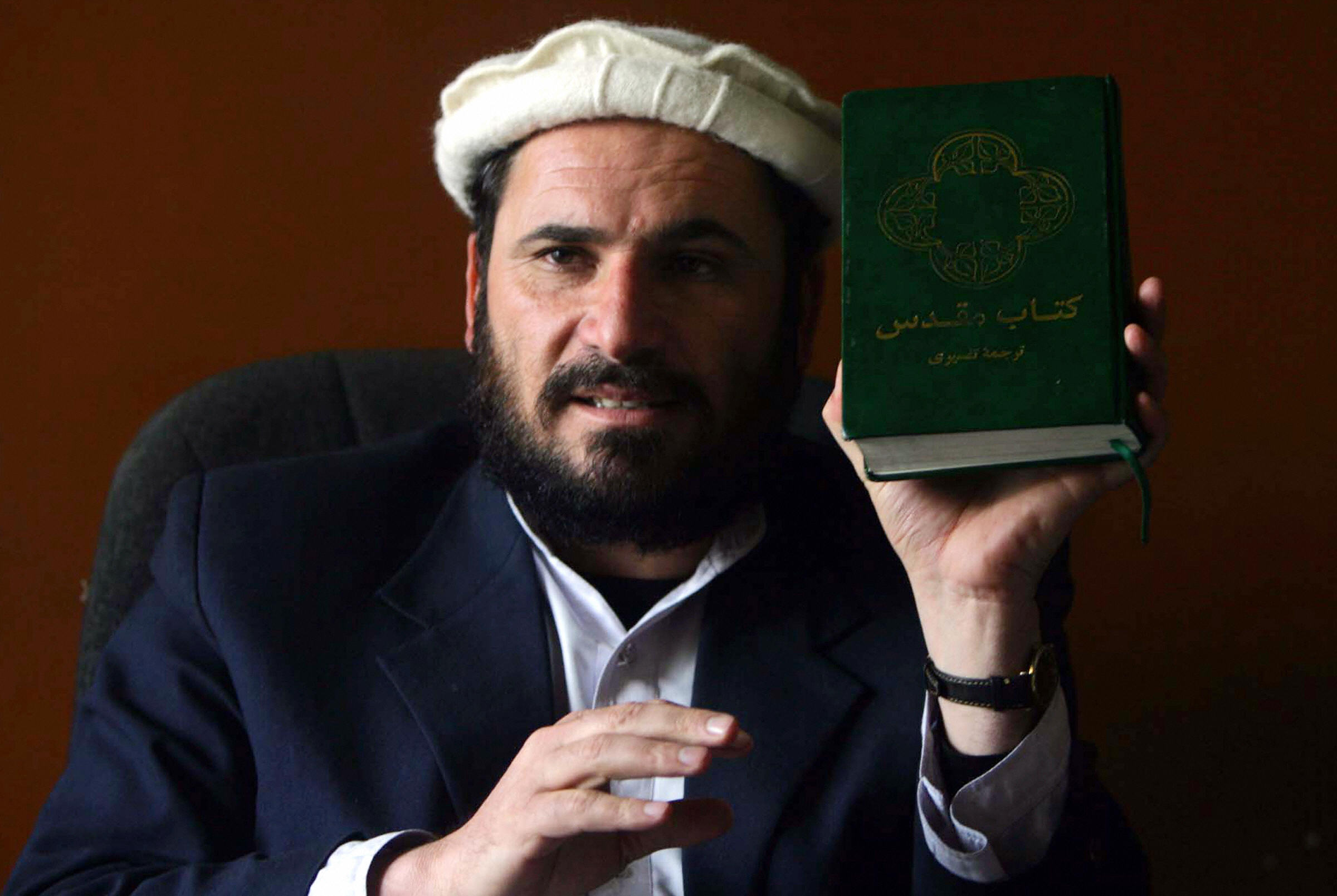 Kabul, AFGHANISTAN: Afghan supreme court judge Ansarullah Mawlavezada holds a Bible in Kabul, 19 March 2006. International pressure is mounting on Afghanistan over the case of a man who faces the death penalty for converting from Islam to Christianity. The trial of Abdul Rahman is being billed as a test of freedom for key US ally Afghanistan, where religion retains a tight grip on society four years after the toppling of the fundamentalist Taliban regime.Washington says it is watching closely how Kabul deals with Rahman, 41, who is believed to be the first convert accused in Afghanistan under strict Islamic Sharia law for refusing to become Muslim again. AFP PHOTO/ Gul Badeen (Photo credit should read GUL BADEEN/AFP via Getty Images)