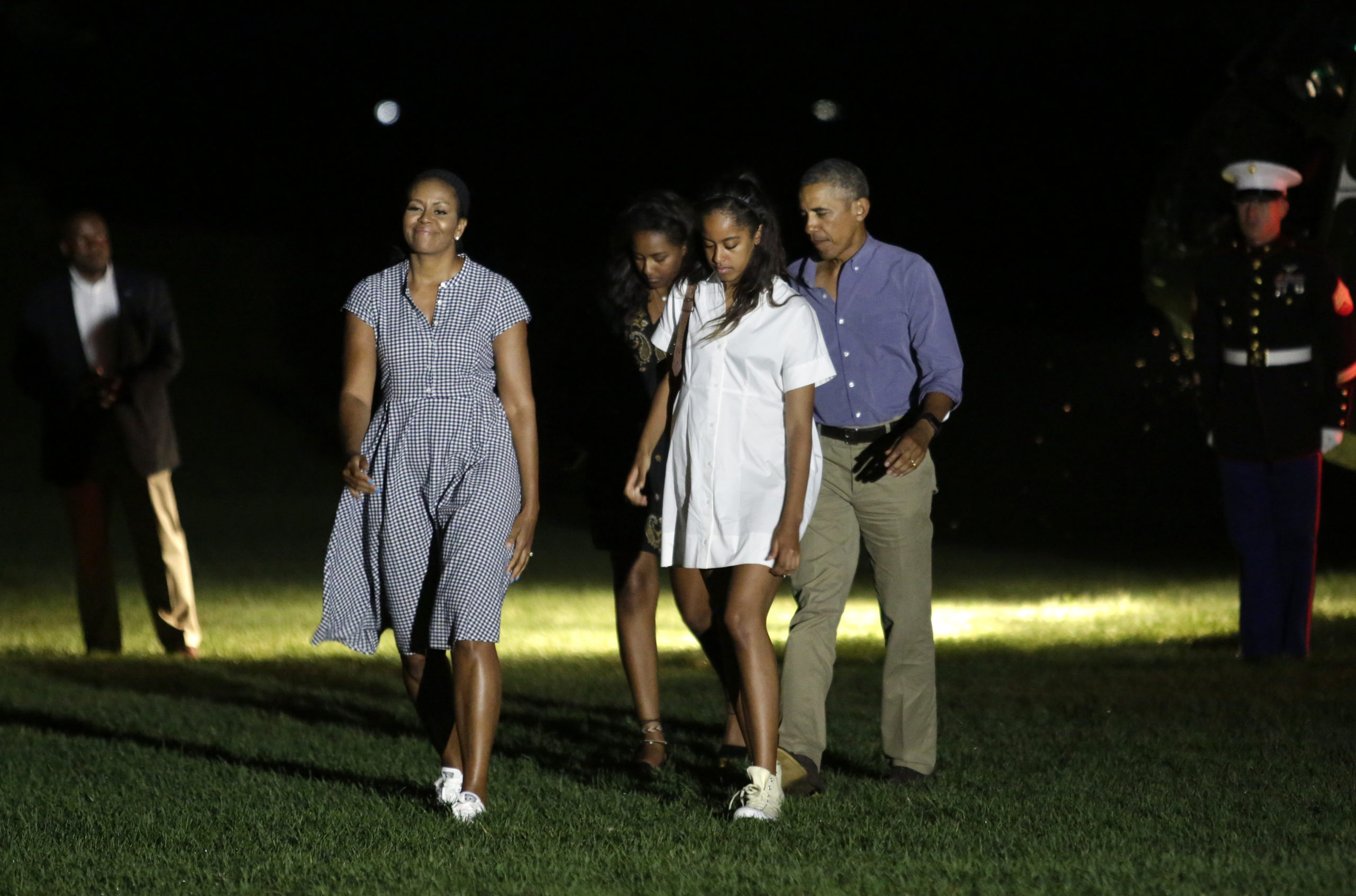 US President Barack Obama waves as he walks with First lady Michelle Obama (L) and their daughters Malia (2nd-R) and Sasha (3rd-R) on the South Lawn of the White House in Washington upon their return from a summer vacation in Martha's Vineyard, Massachusetts on August 21, 2016. / AFP / YURI GRIPAS (Photo credit should read YURI GRIPAS/AFP via Getty Images)