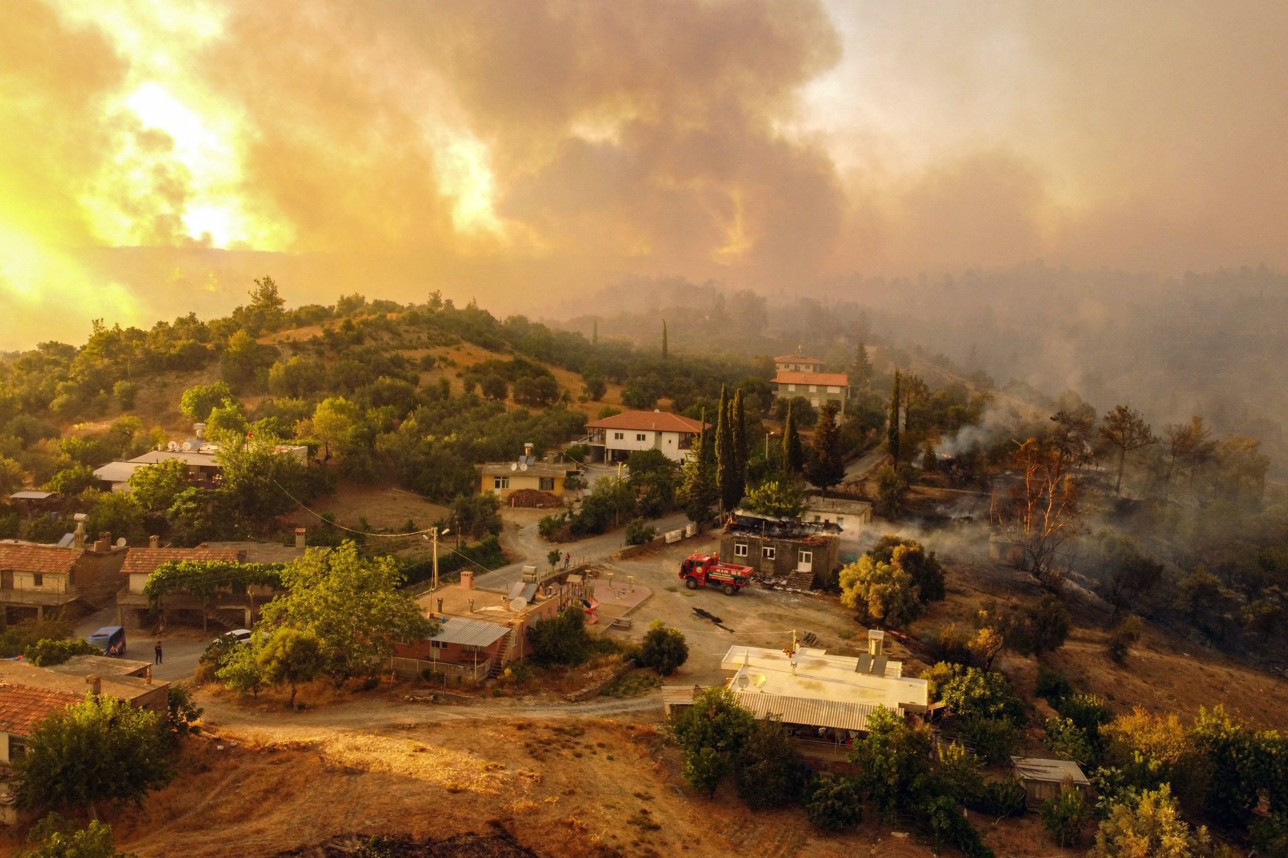 This aerial photograph shows houses surrounded by a wildfire which engulfed a Mediterranean resort region on Turkey's southern coast near the town of Manavgat, on July 30, 2021. - At least three people were reported dead on July 29, 2021 and more than 100 injured as firefighters battled blazes engulfing a Mediterranean resort region on Turkey's southern coast. Officials also launched an investigation into suspicions that the fires that broke out Wednesday in four locations to the east of the tourist hotspot Antalya were the result of arson. (Photo by -/AFP via Getty Images)