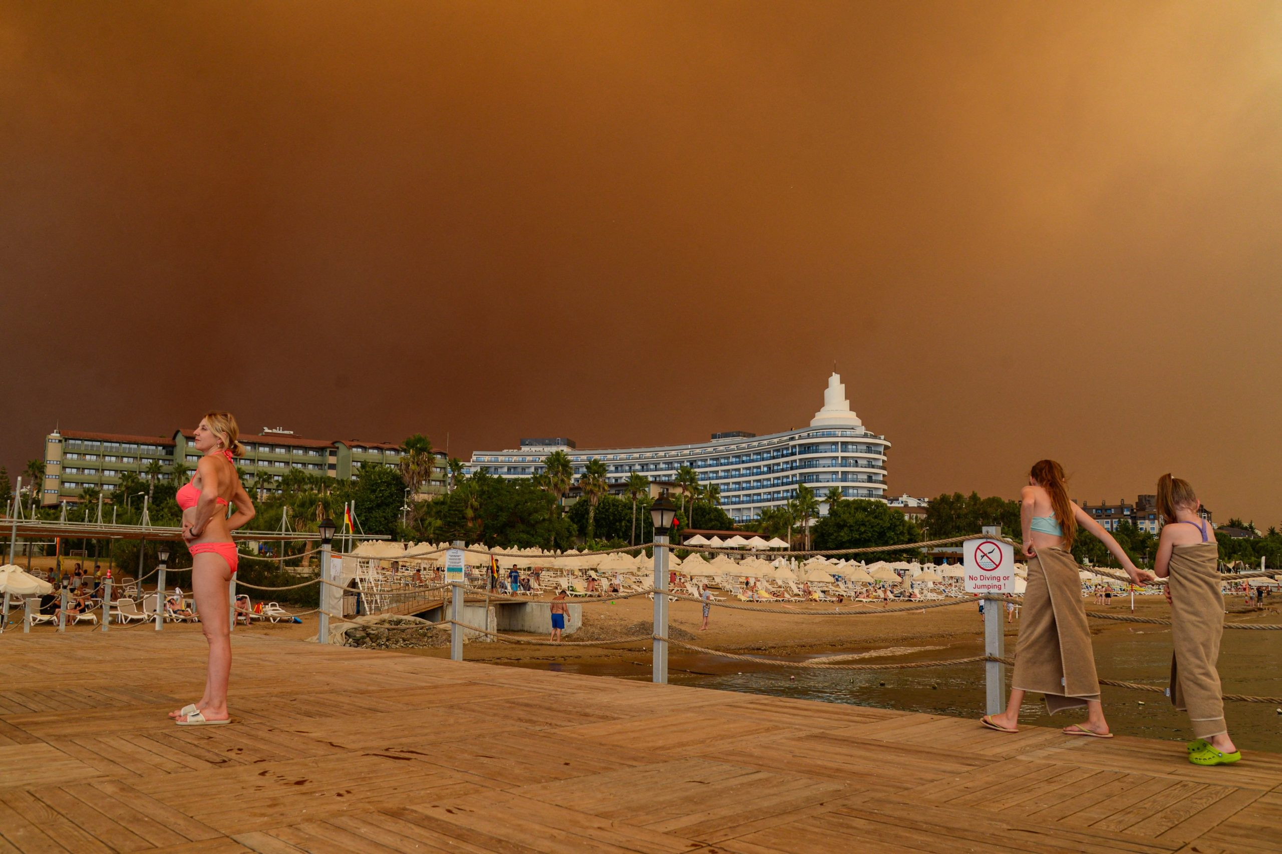 Dark smoke drifts over a hotel complex during a massive forest fire which engulfed a Mediterranean resort region on Turkey's southern coast near the town of Manavgat, on July 29, 2021. - At least three people were reported dead on July 29, 2021 and more than 100 injured as firefighters battled blazes engulfing a Mediterranean resort region on Turkey's southern coast. Officials also launched an investigation into suspicions that the fires that broke out Wednesday in four locations to the east of the tourist hotspot Antalya were the result of arson. (Photo by ILYAS AKENGIN/AFP via Getty Images)