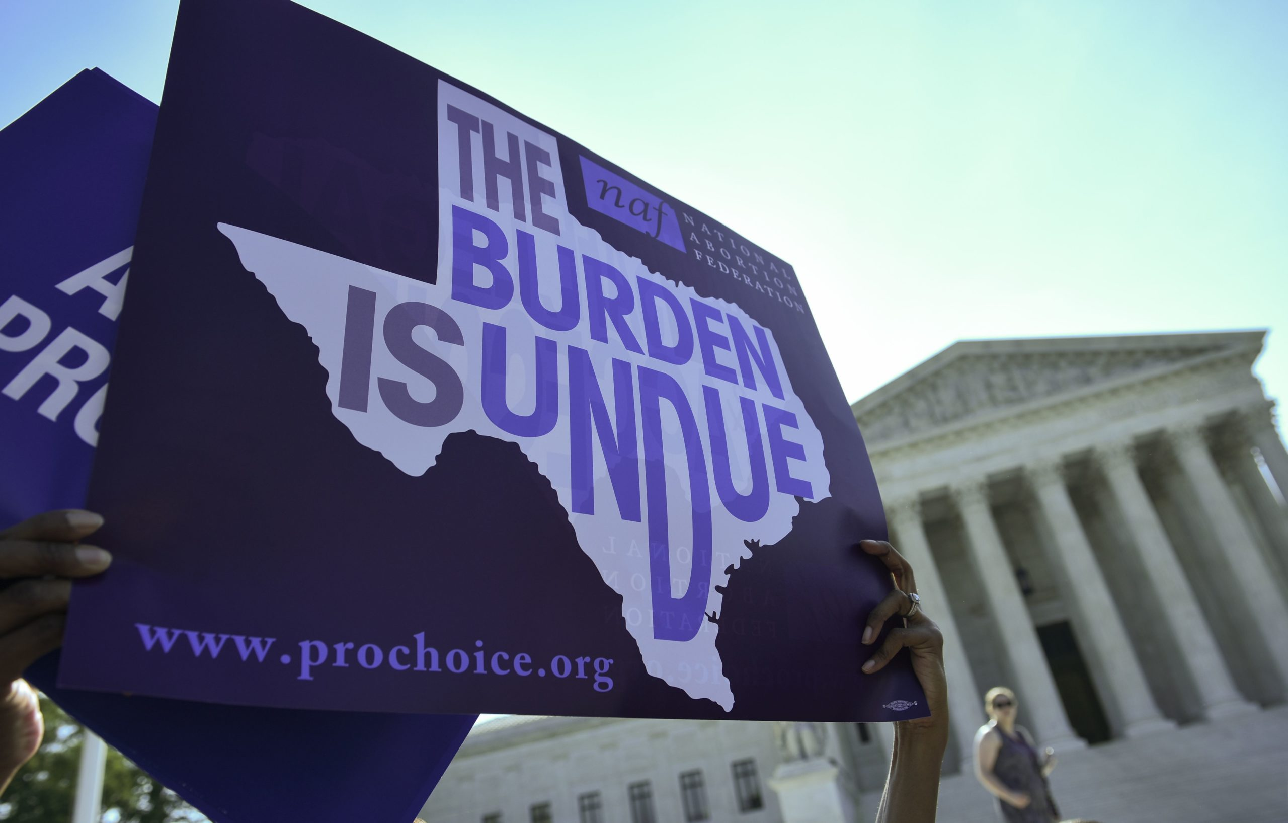 """An abortion rights activist holds placards outside of the US Supreme Court before the Court struck down a Texas law placing restrictions on abortion clinics on June 27, 2016 in Washington, DC. The US Supreme Court on Monday struck down a Texas law placing a raft of restrictions on abortion clinics, handing a major victory to the """"pro-choice"""" camp in the country's most important ruling on the divisive issue in a generation. / AFP / MANDEL NGAN (Photo credit should read MANDEL NGAN/AFP via Getty Images)"""
