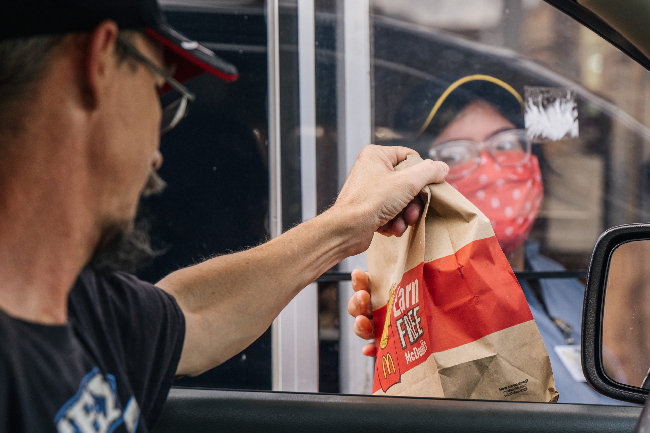 A customer receives his food in a McDonald's drive-thru on July 28, 2021 in Houston, Texas. (Photo by Brandon Bell/Getty Images)