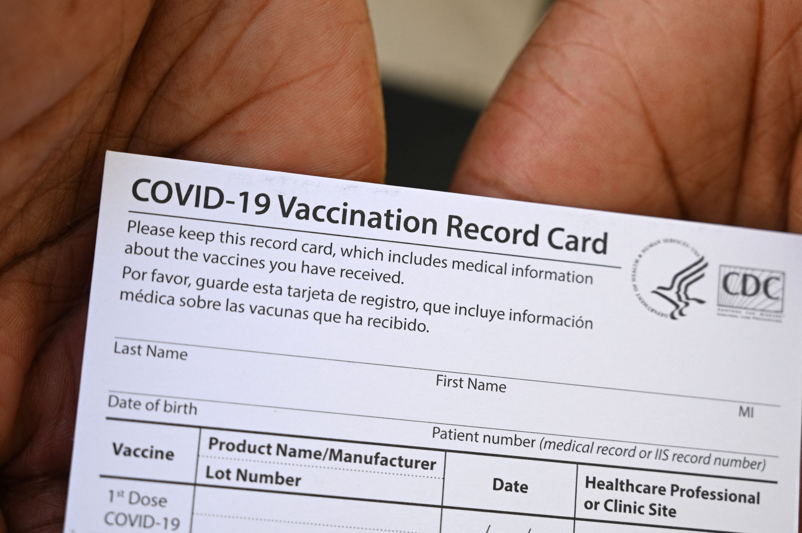 A healthcare worker displays a Covid-19 Vaccination Record Card. (Photo by ROBYN BECK/AFP via Getty Images)