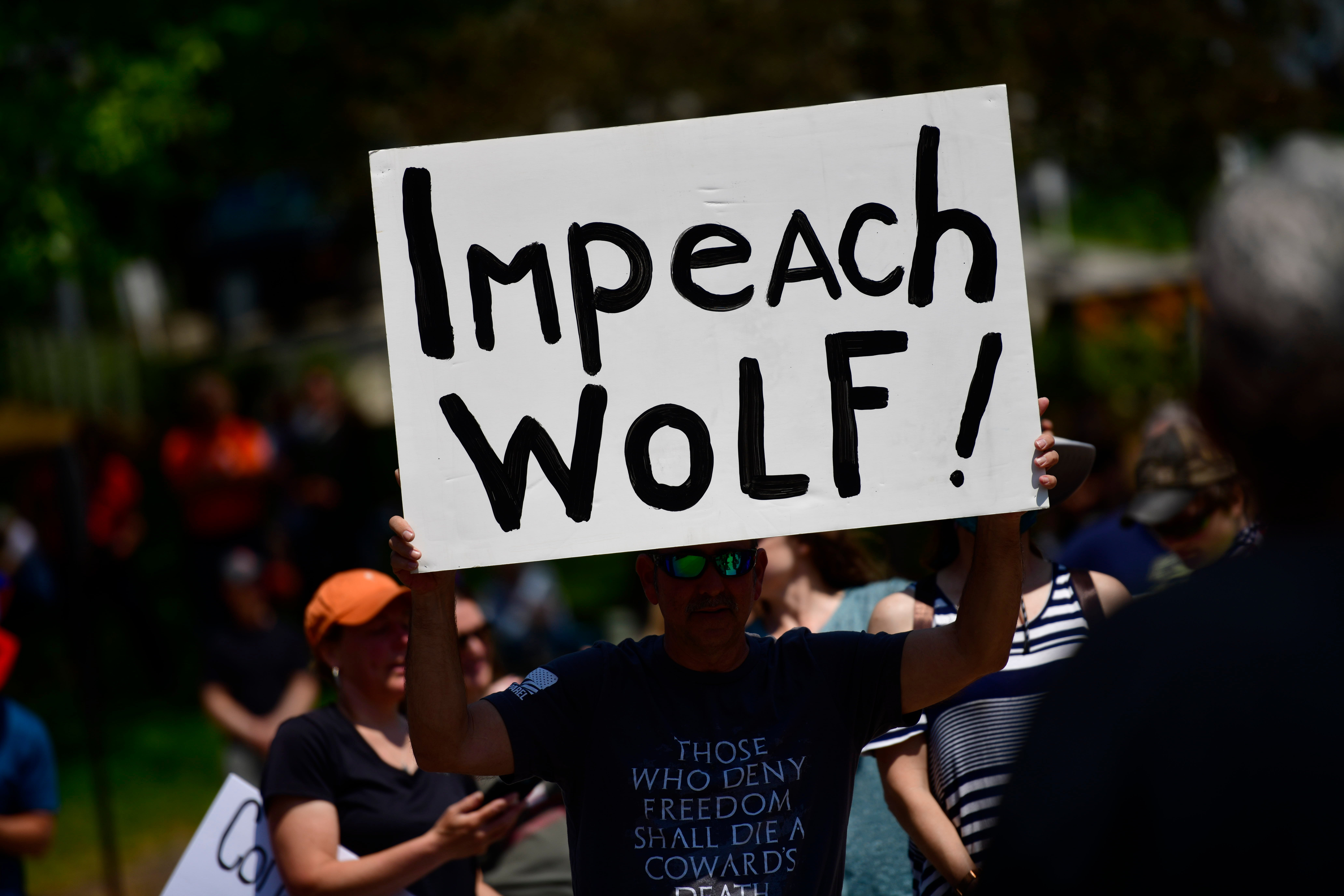 """A demonstrator holds a sign stating """"Impeach Wolf!"""" during a protest rally against Pennsylvania Governor Tom Wolf. (Photo by Mark Makela/Getty Images)"""