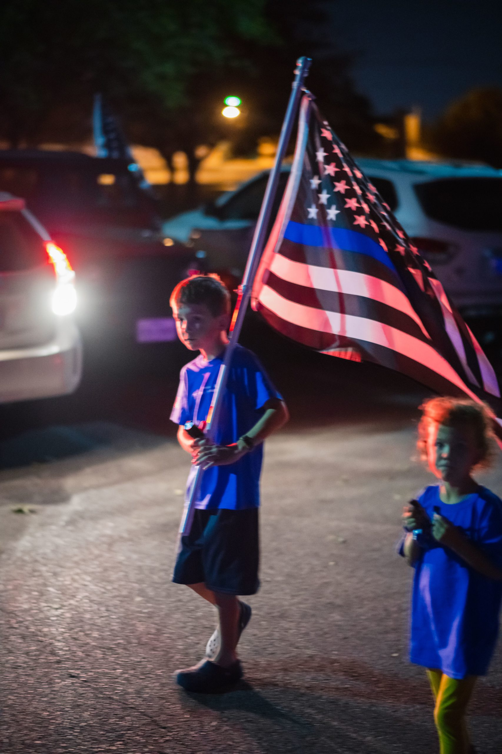 A young boy holds a thin blue line flag at the United by the Blue Line Vigil organized by the El Paso Police Wives and Family Support Organization at Album Park in El Paso, Texas on November 7, 2020. (Photo by JUSTIN HAMEL/AFP via Getty Images)